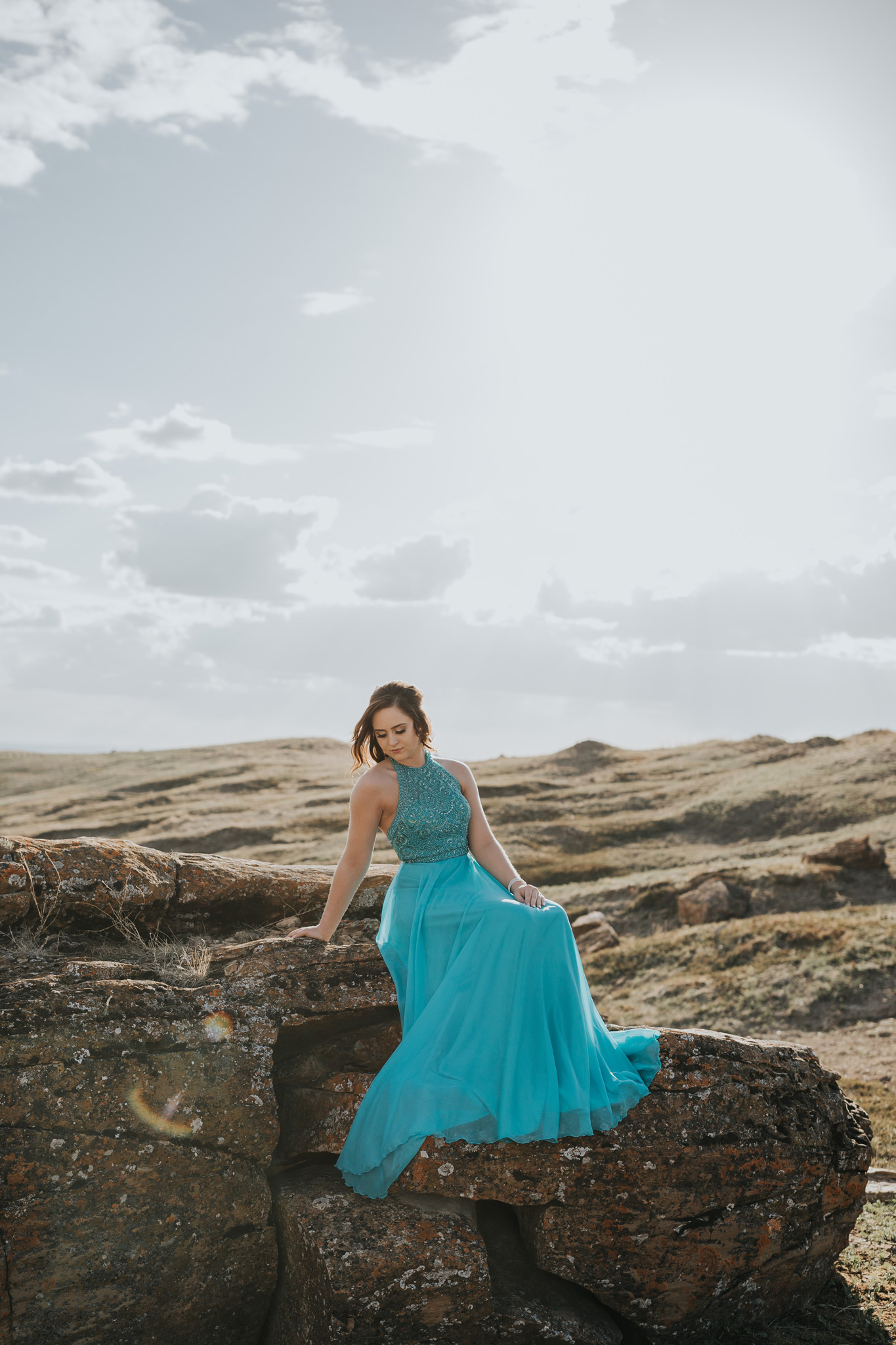 red rock coulee grad girl sitting on large rock looking down
