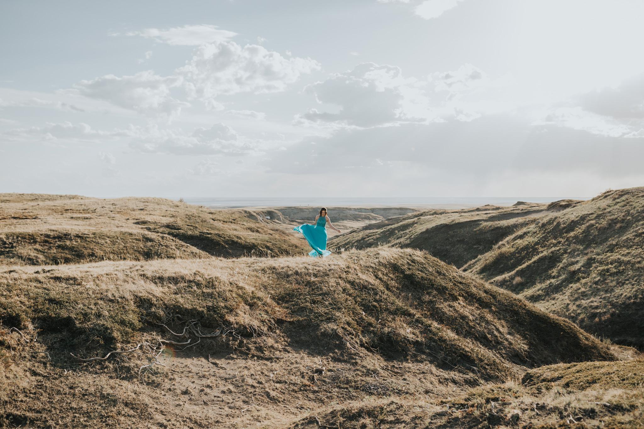 girl twirling in dress in distance landscape