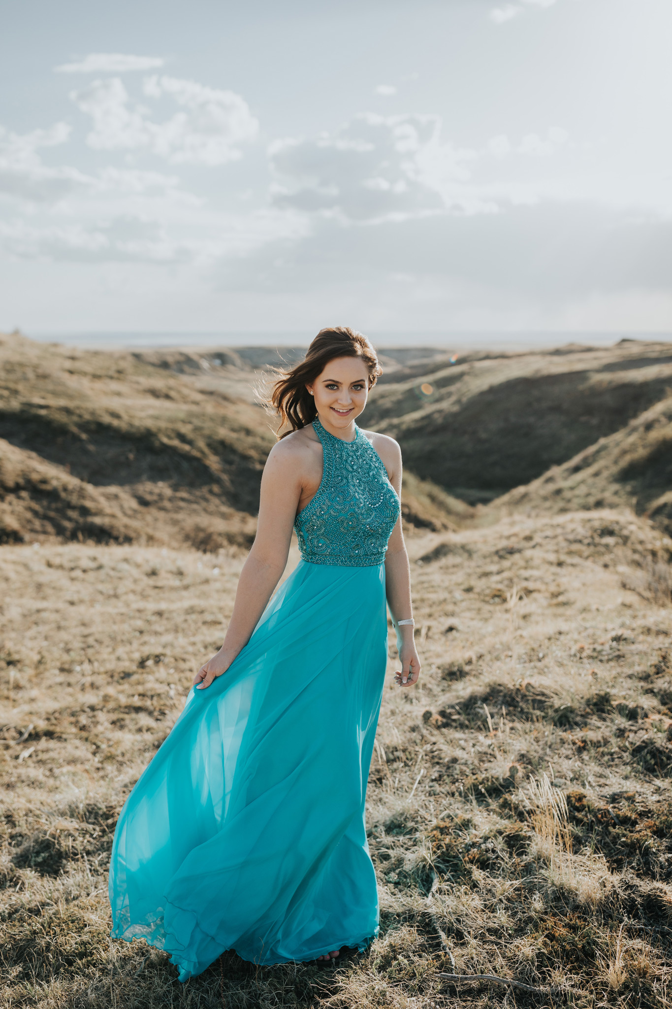 grad girl smiling holding dress as wind blows