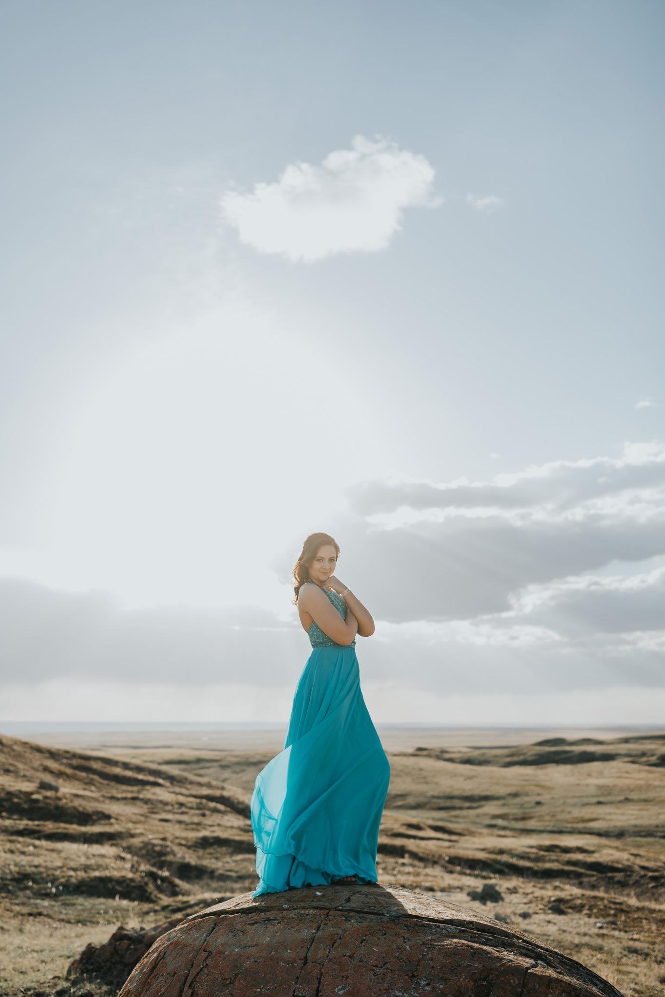 girl posing on large rock dress skirt blowing in wind