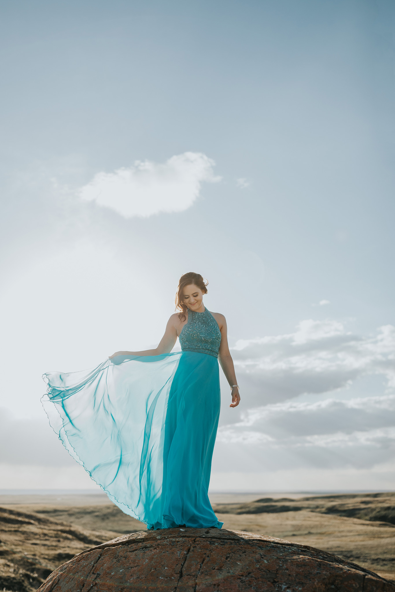 girl standing on large rock prom dress blowing in the wind