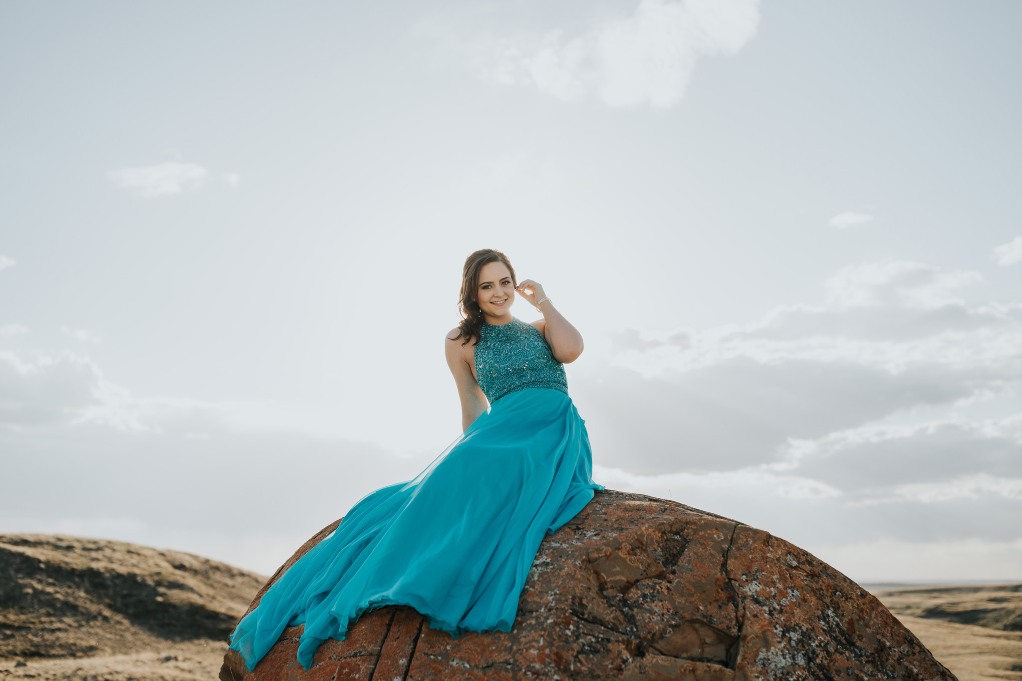 girl in prom dress sitting on large rock smiling