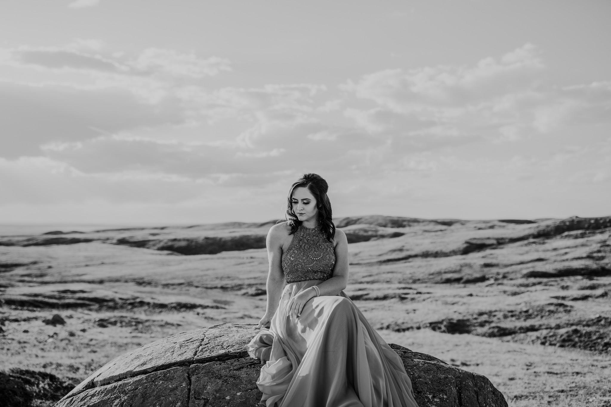 graduate sitting on large rock black and white