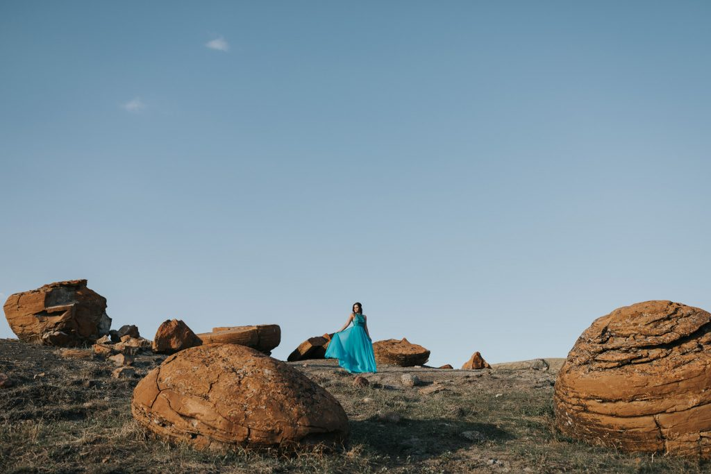 girl in grad dress standing surrounded by large red rocks