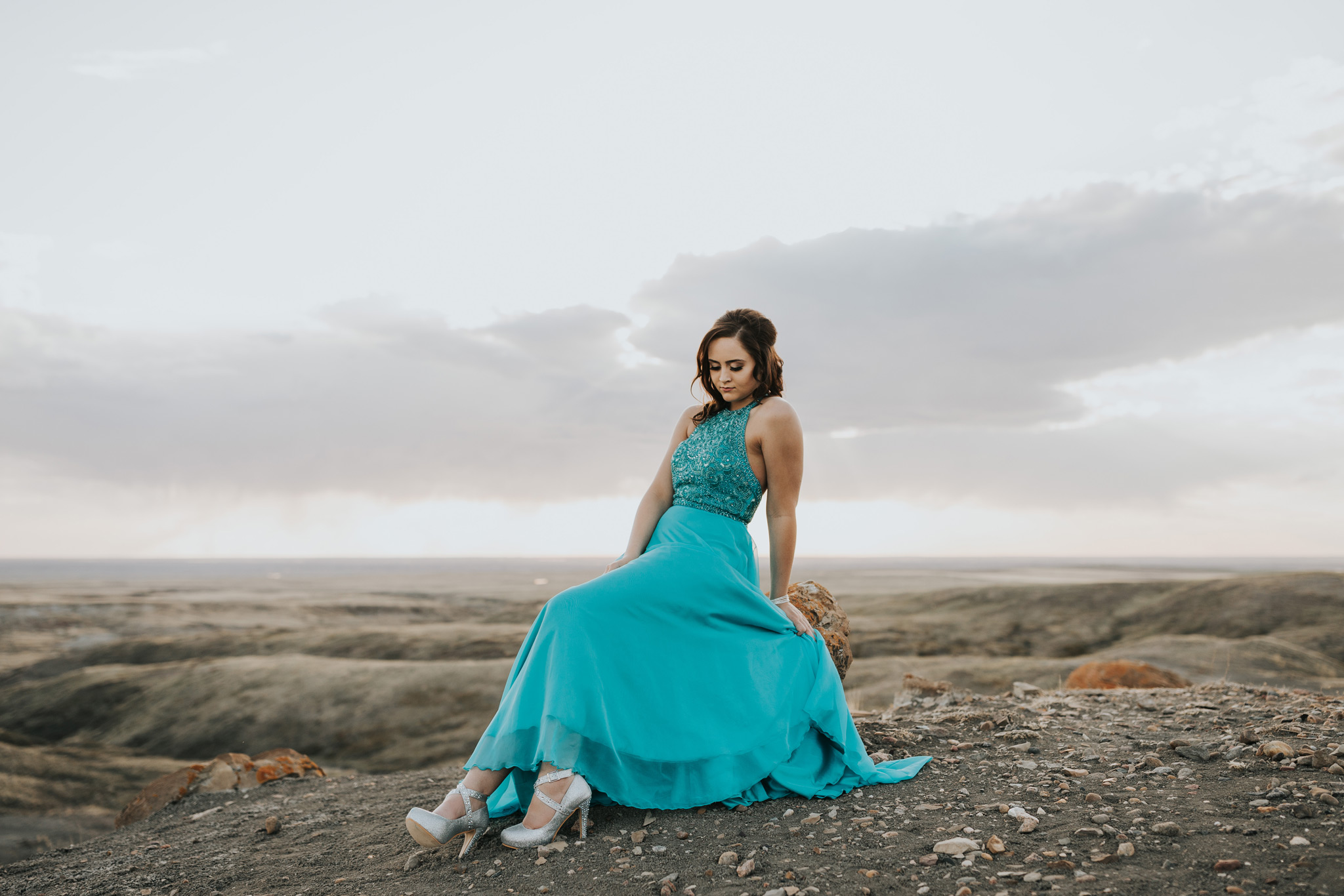 graduate in turquoise prom dress with beading on top looking down at sparkly high heels