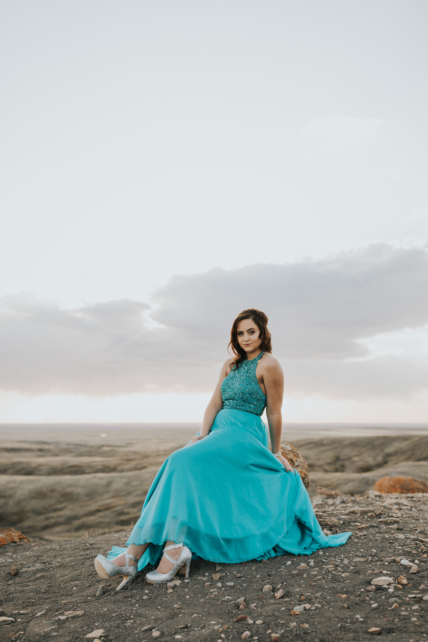 graduate in turquoise prom dress with beading on top and sparkly silver shoes