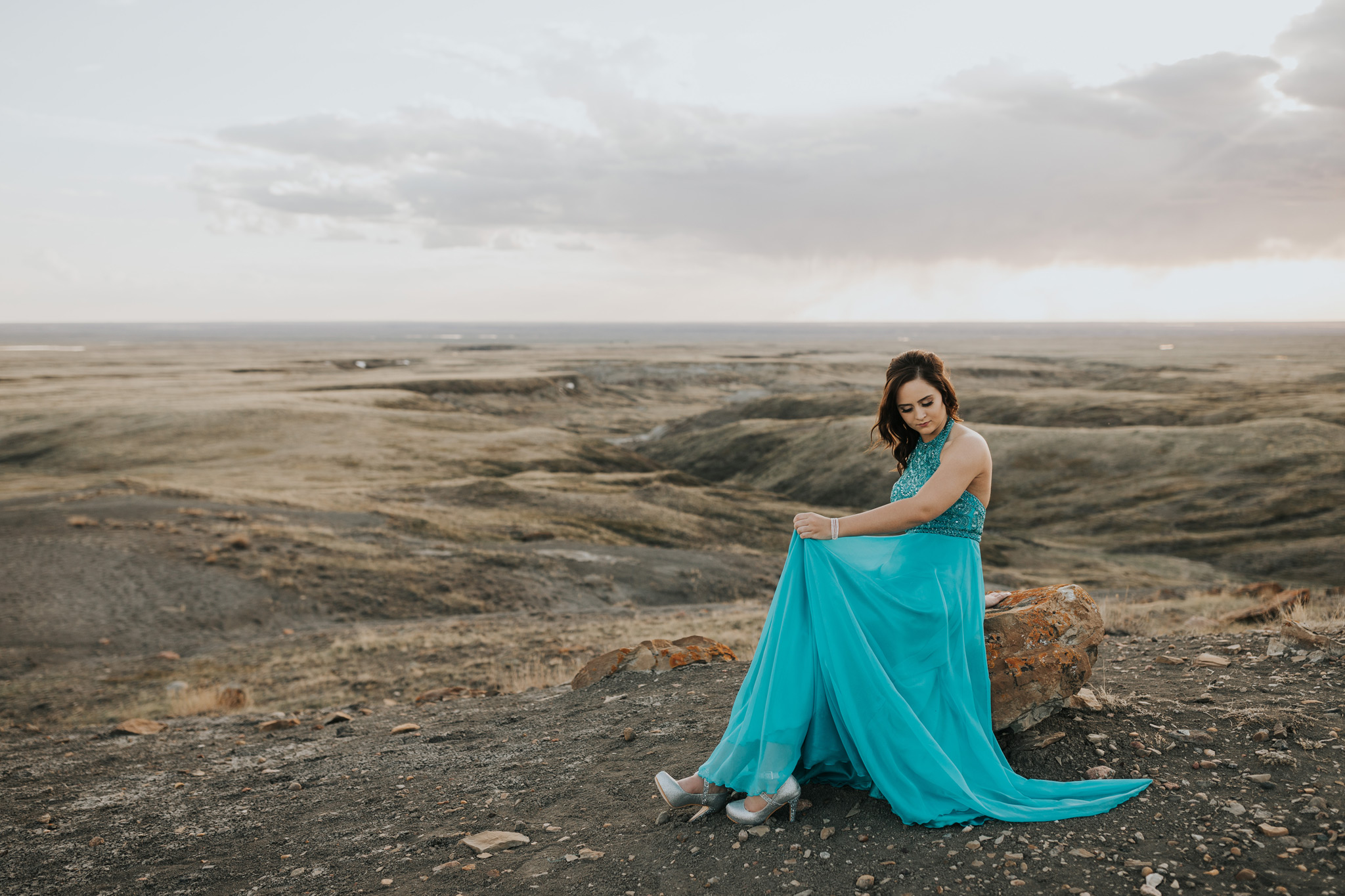 grad girl sitting on rock moving dress skirt with view of landscape