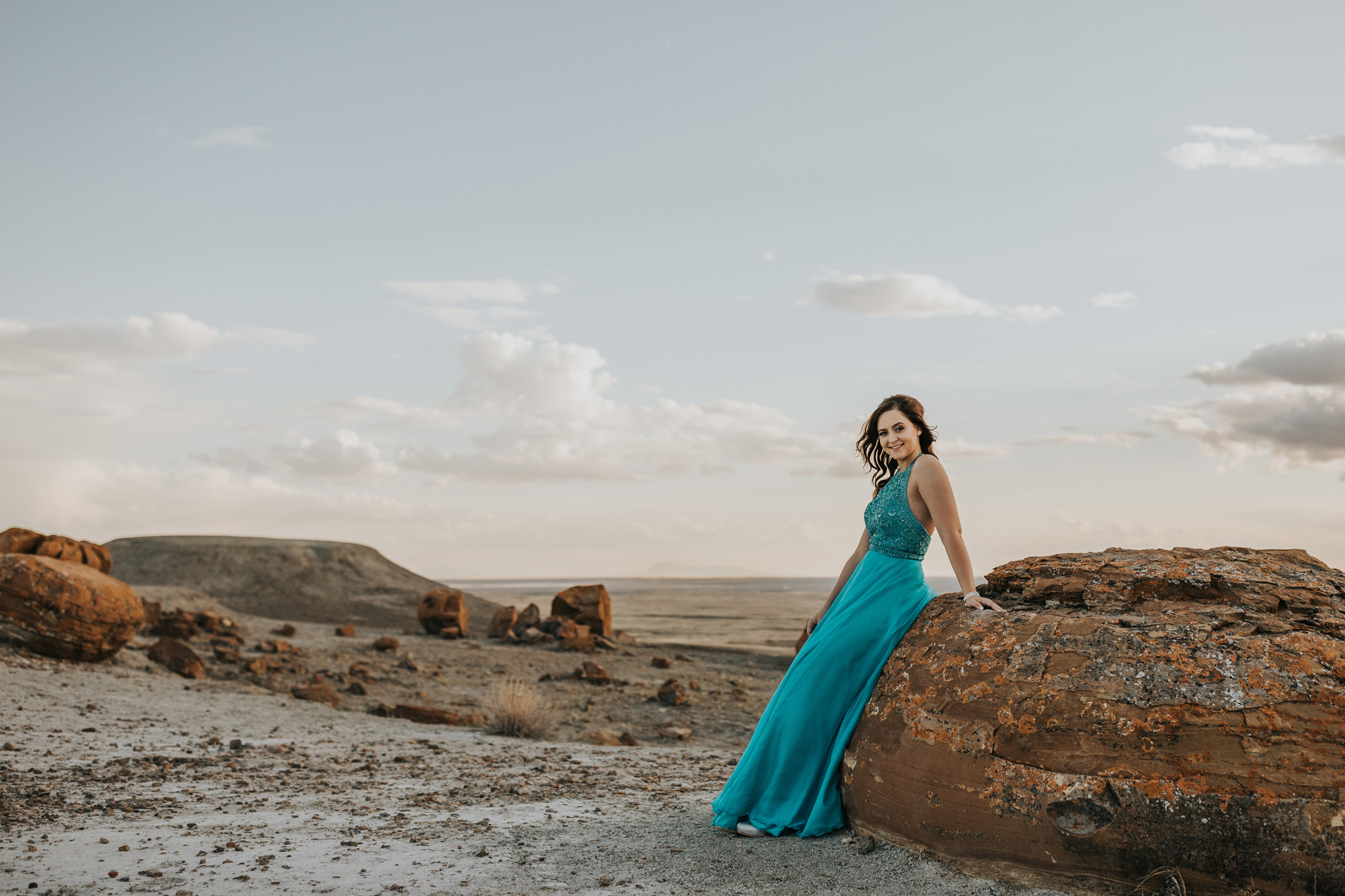 graduate leaning against large rock smiling with sweetgrass hills of montana in background