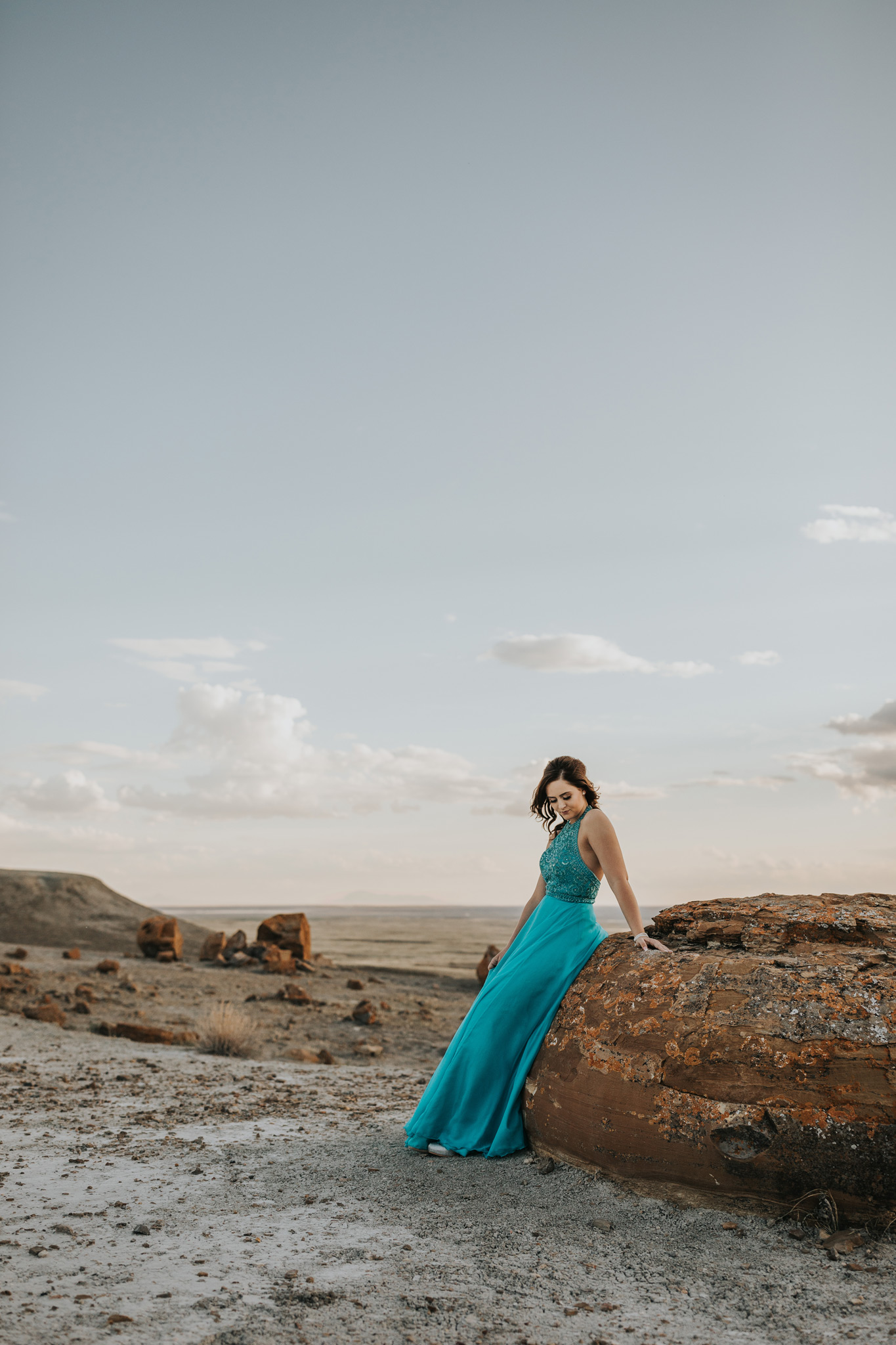 girl in dress standing leaning against large red rock looking down