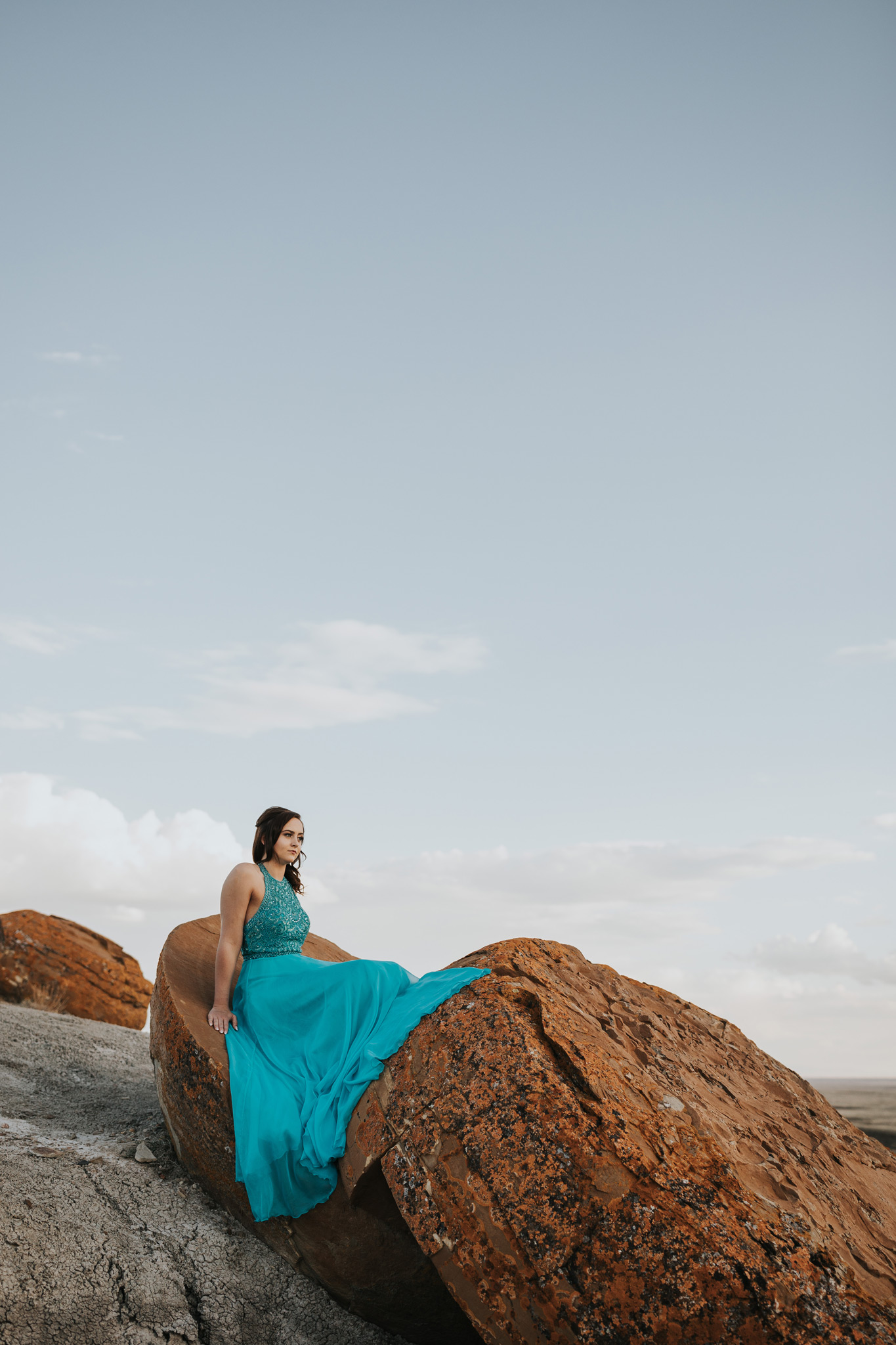 teenager sitting on huge red rock dress draped gracefully over edge