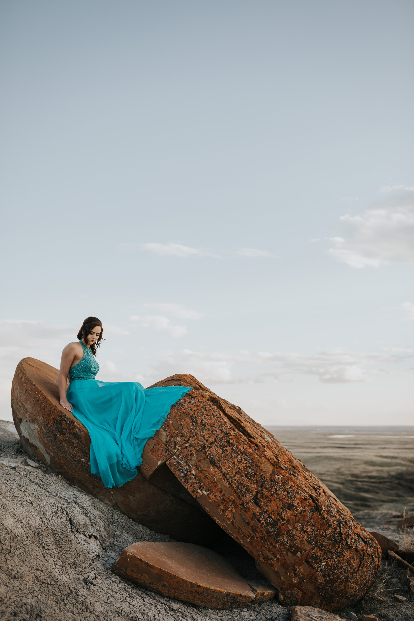 girl sitting on large red rock dress draped over edge