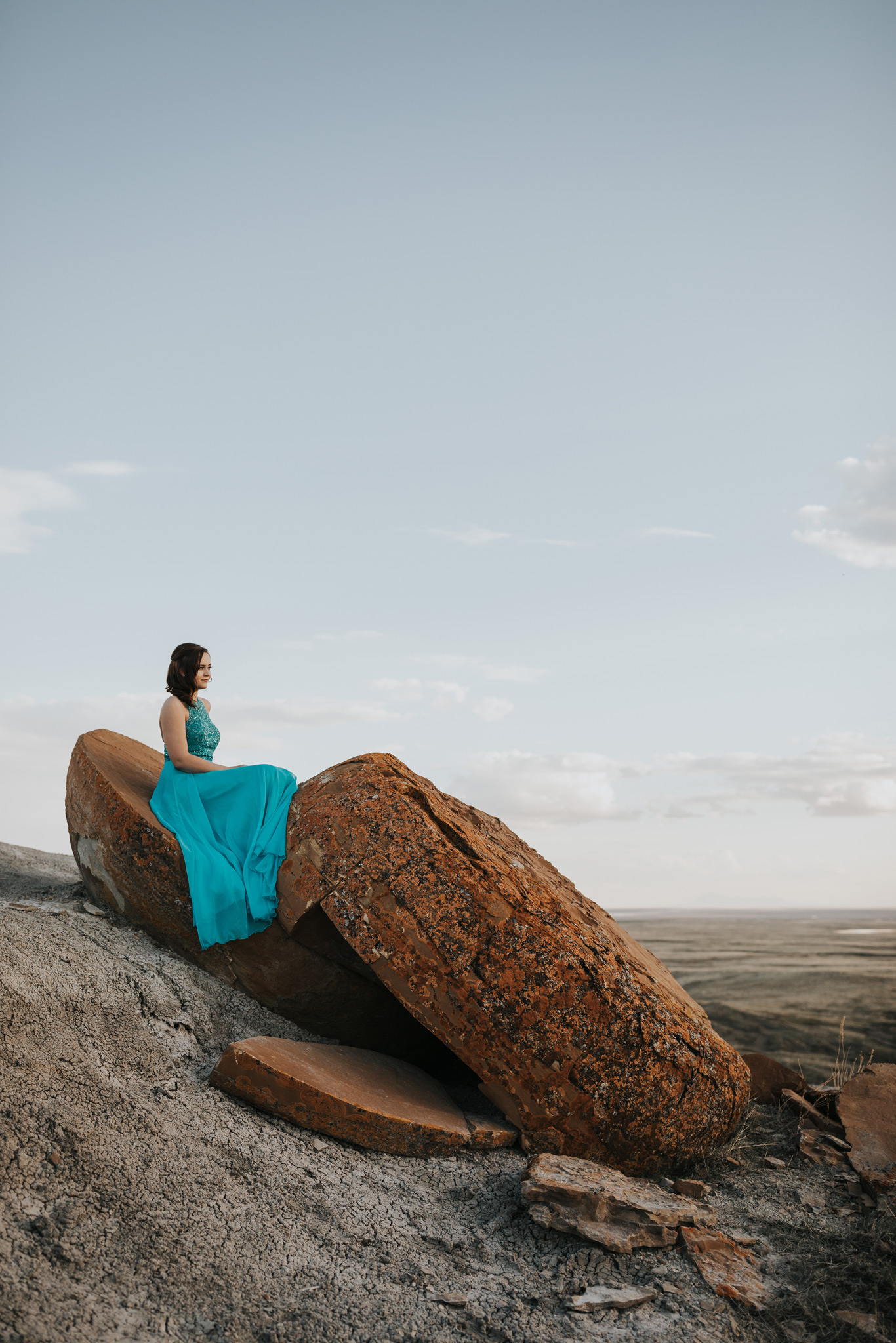 graduate sitting on large red rock