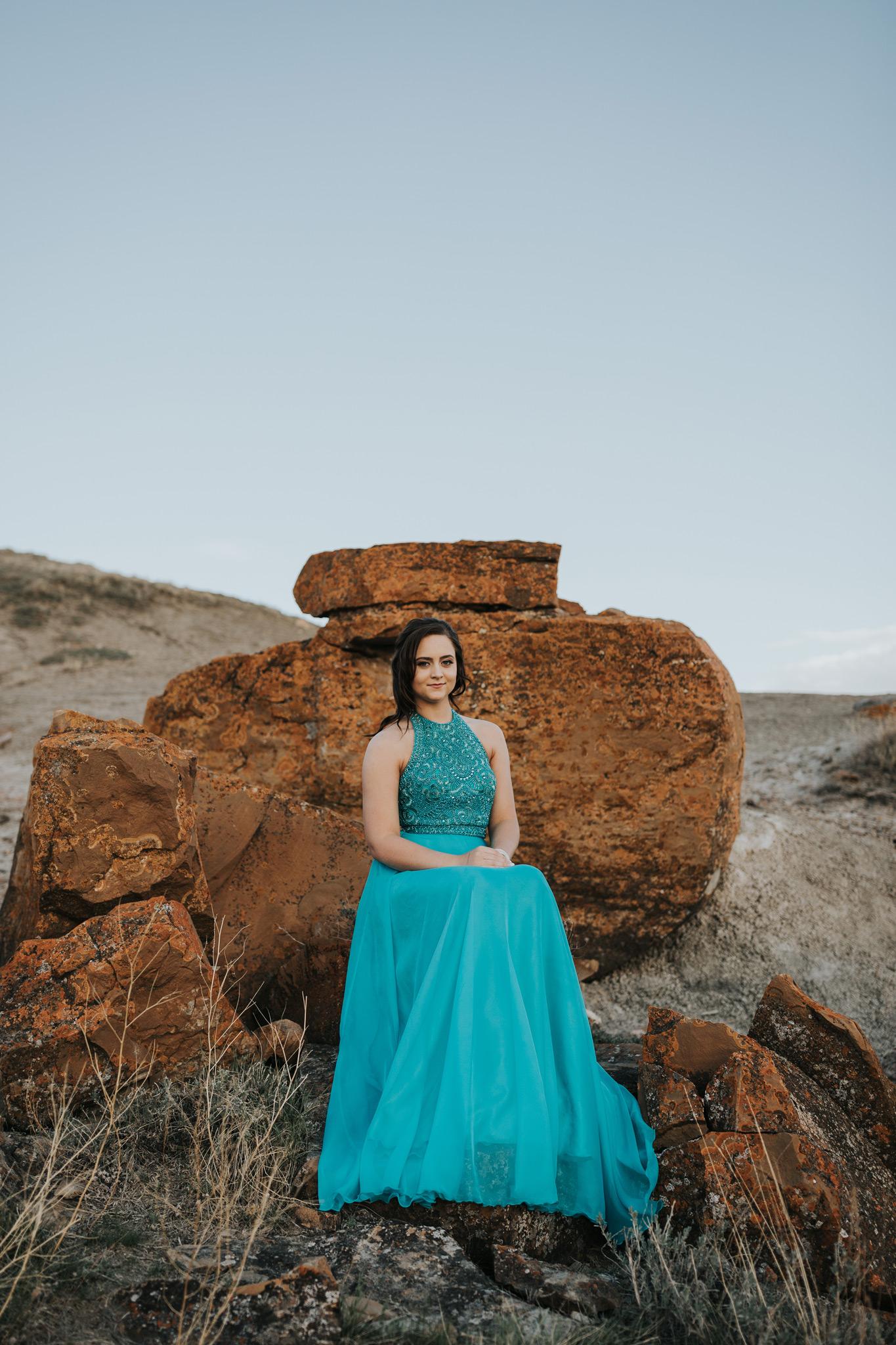 grad girl sitting on rocks resembling a throne