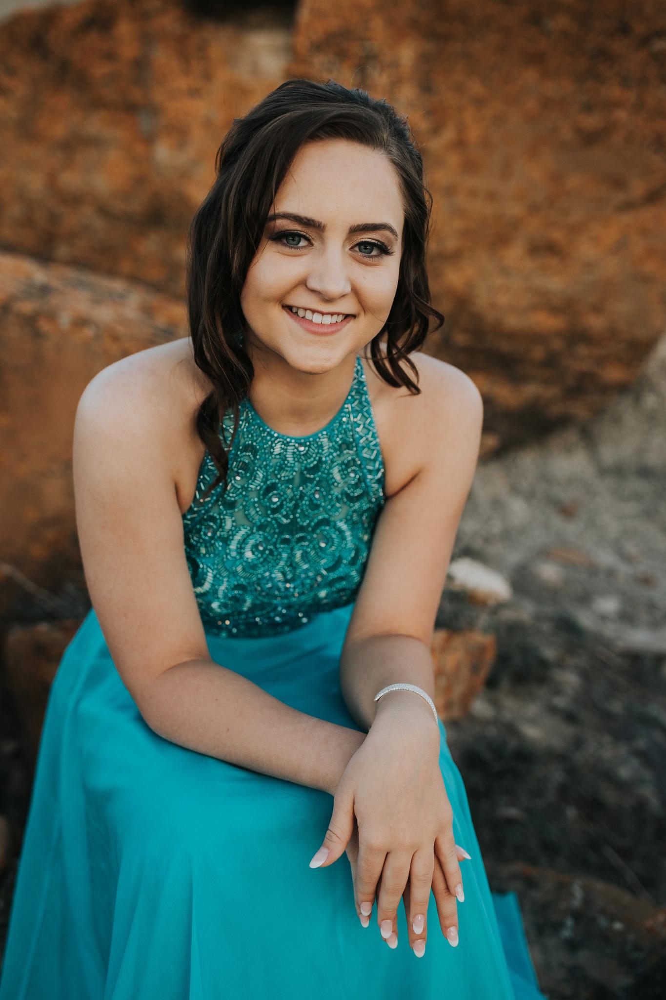 beautiful graduate sitting leaning forward smiling