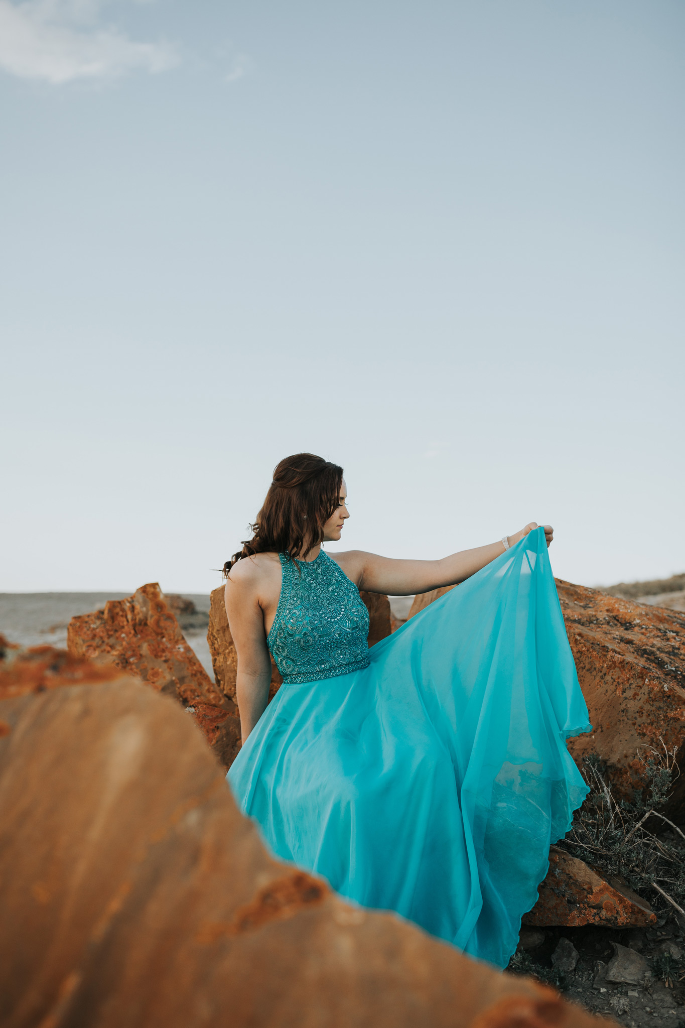 adventurous grad photo holding up skirt of dress in one hand