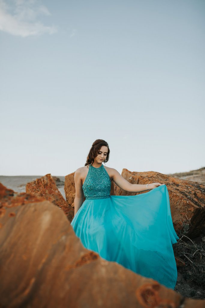 beautiful senior girl sitting in rock formation holding up skirt of dress