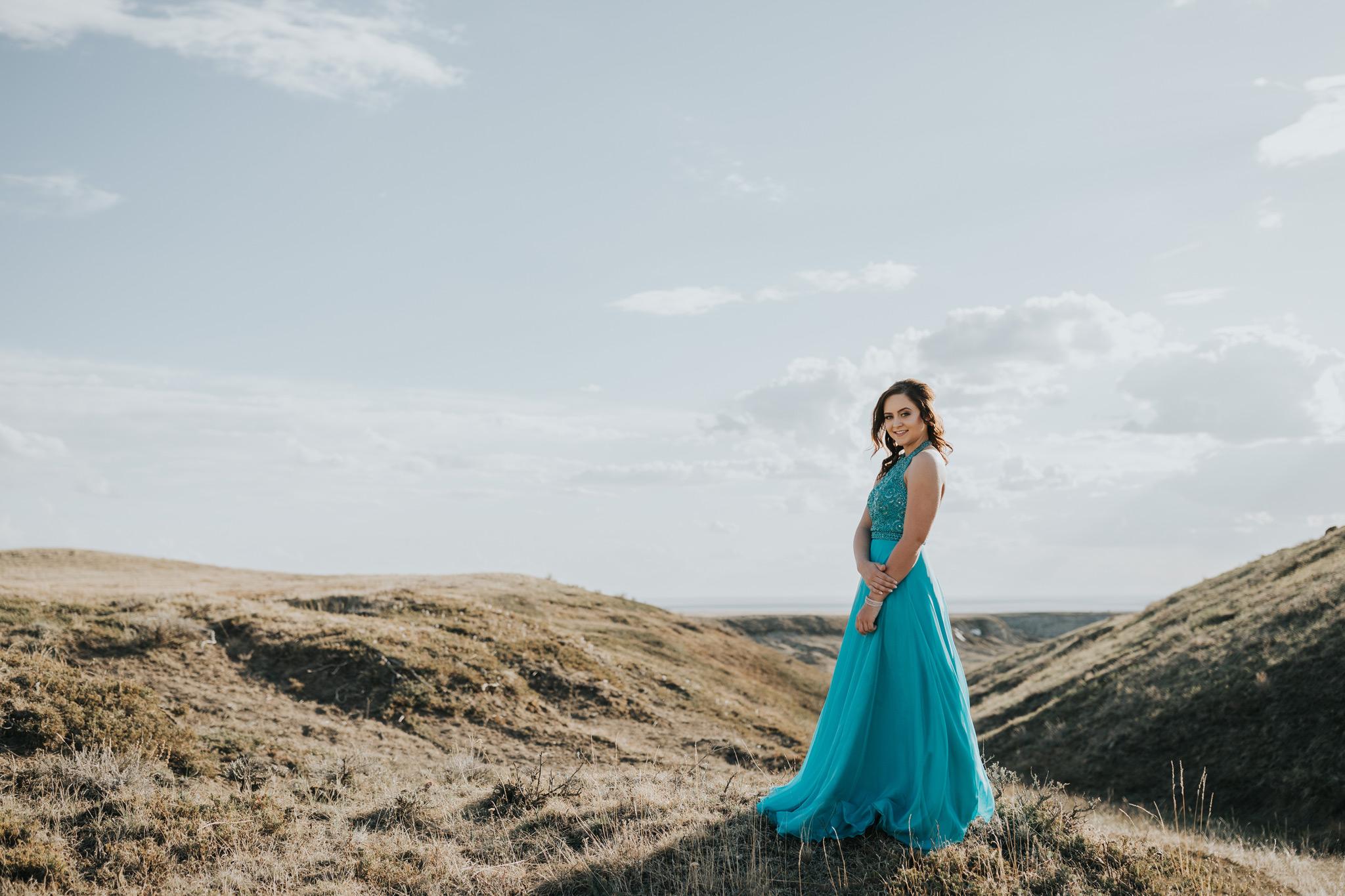 girl standing in grad dress smiling sunset