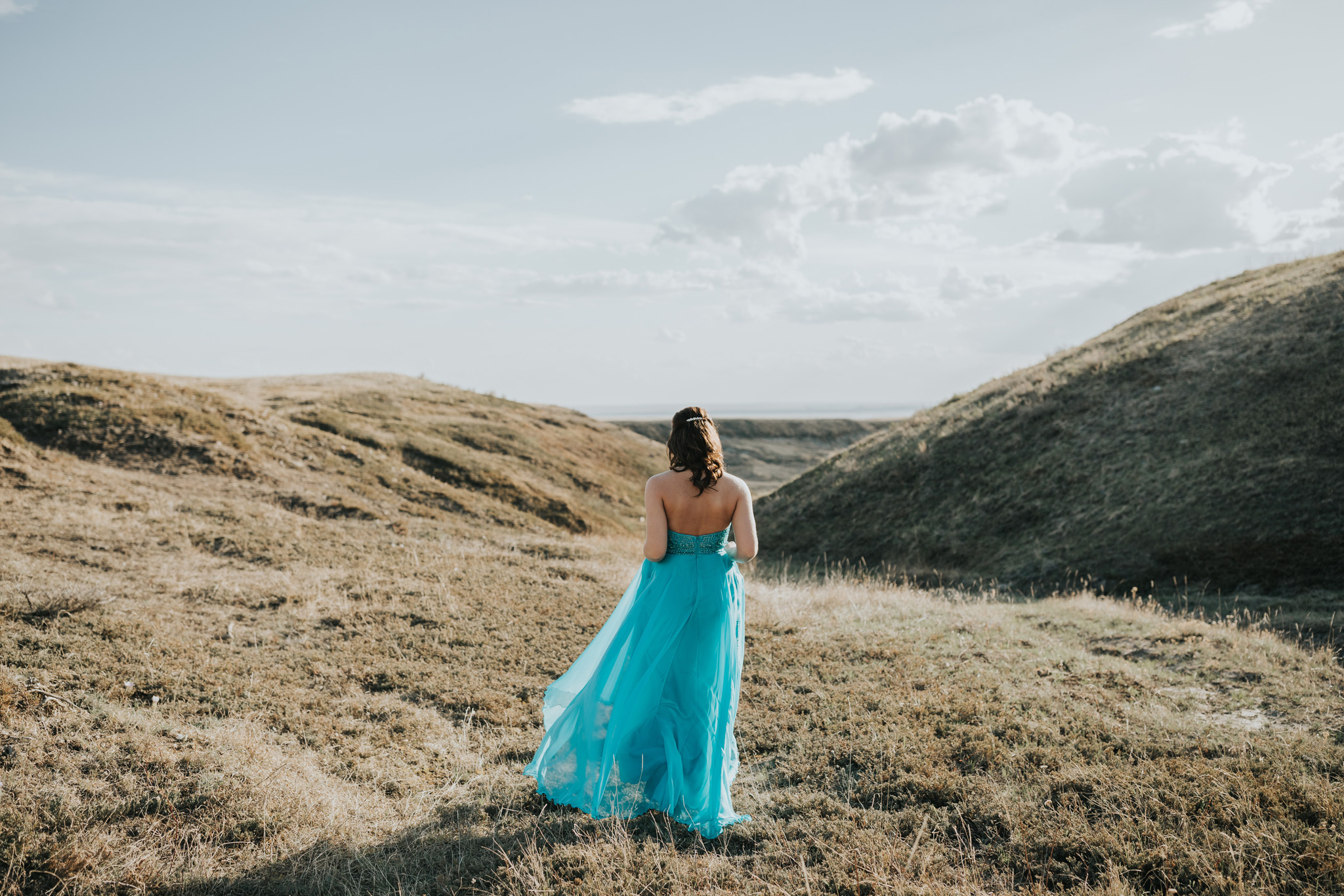 girl in grad dress walking out into landscape coulee