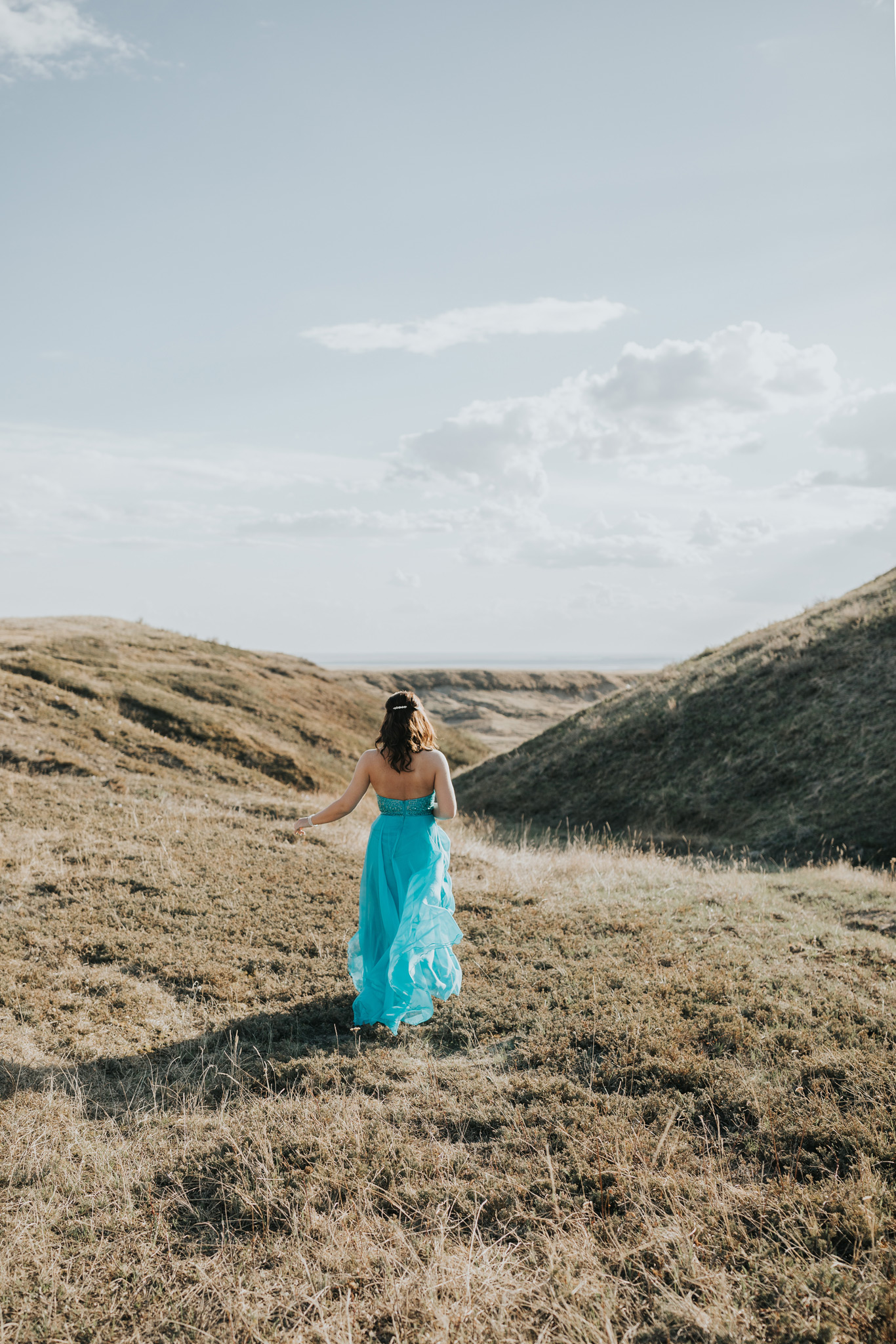 girl in grad dress running out into landscape coulee
