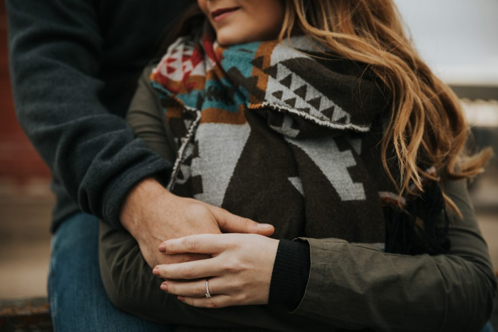 closeup engaged couple holding hands ring photo