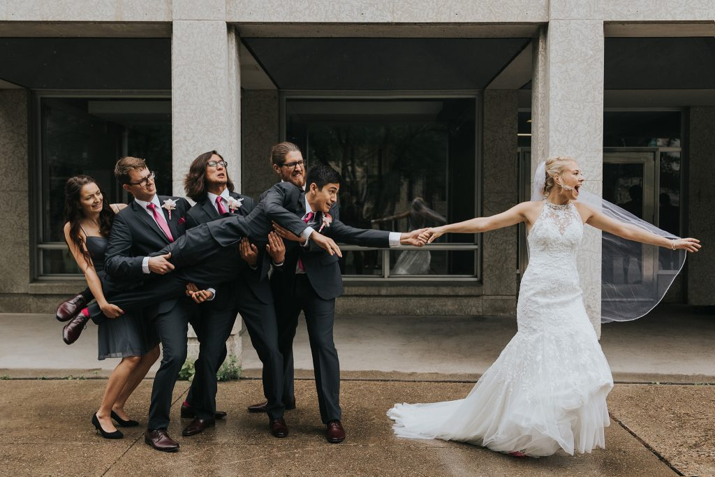 fun wedding bride pulling groom held by groomsmen
