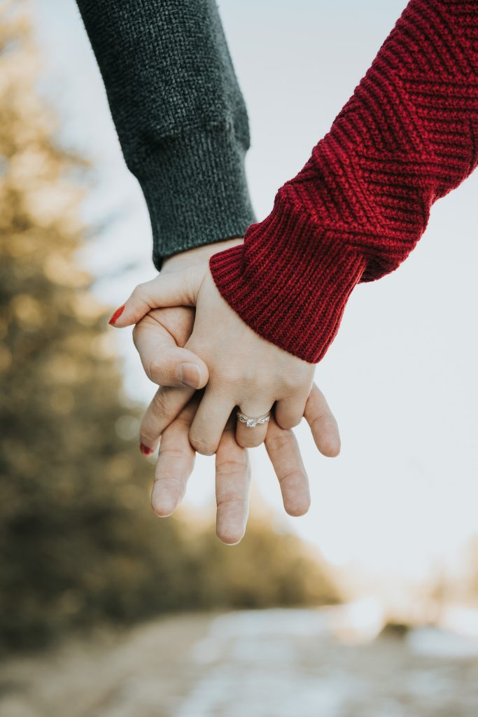 closeup of couple holding hands engagement ring