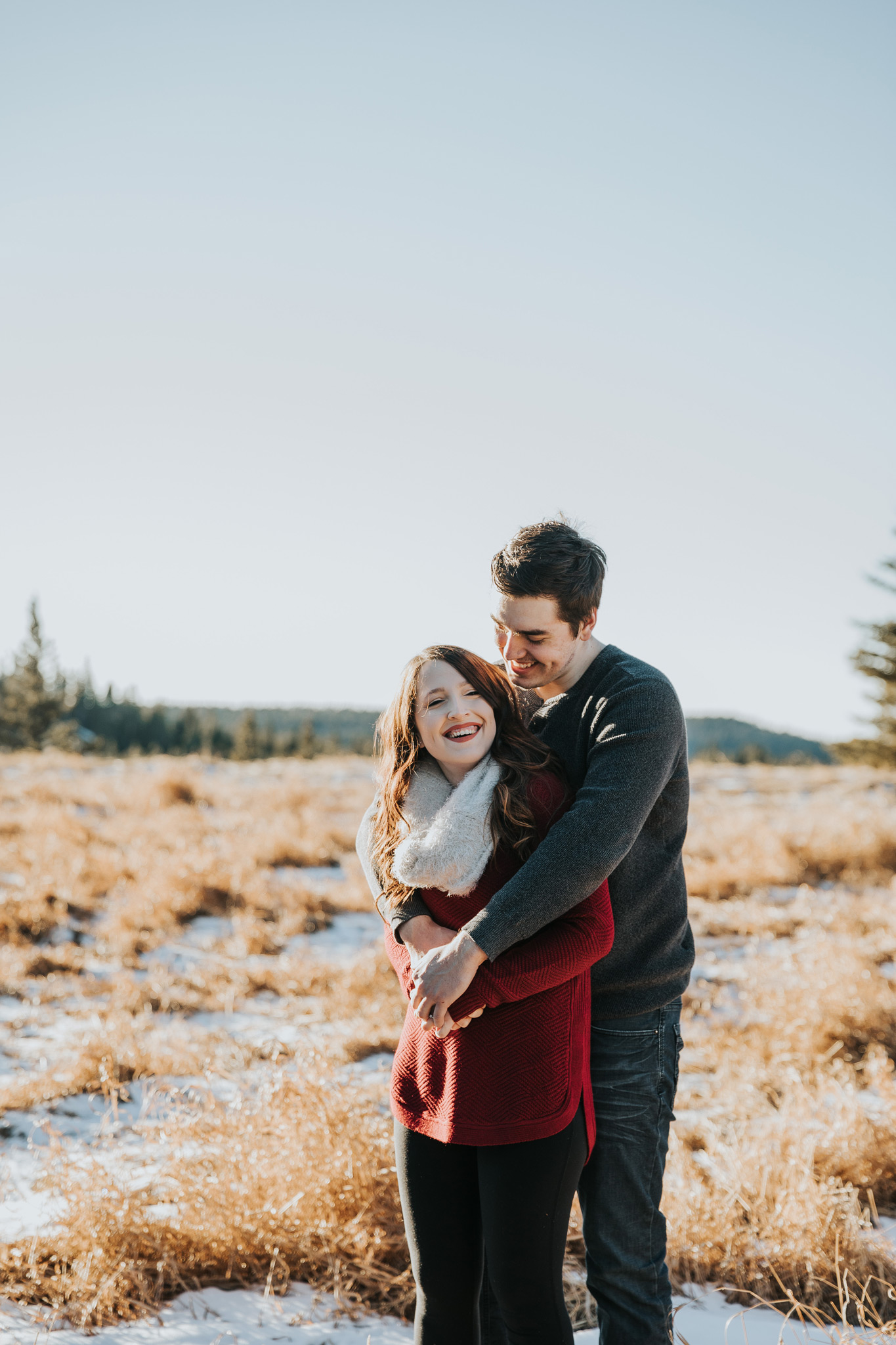 man embraces girl from behind laughing engagement photo