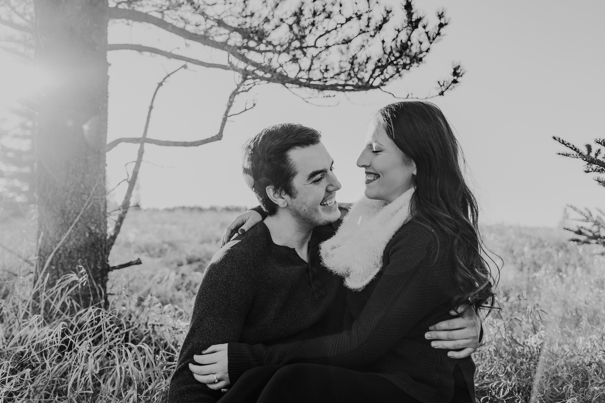 couple sitting in tall grass laughing elkwater engagement photo