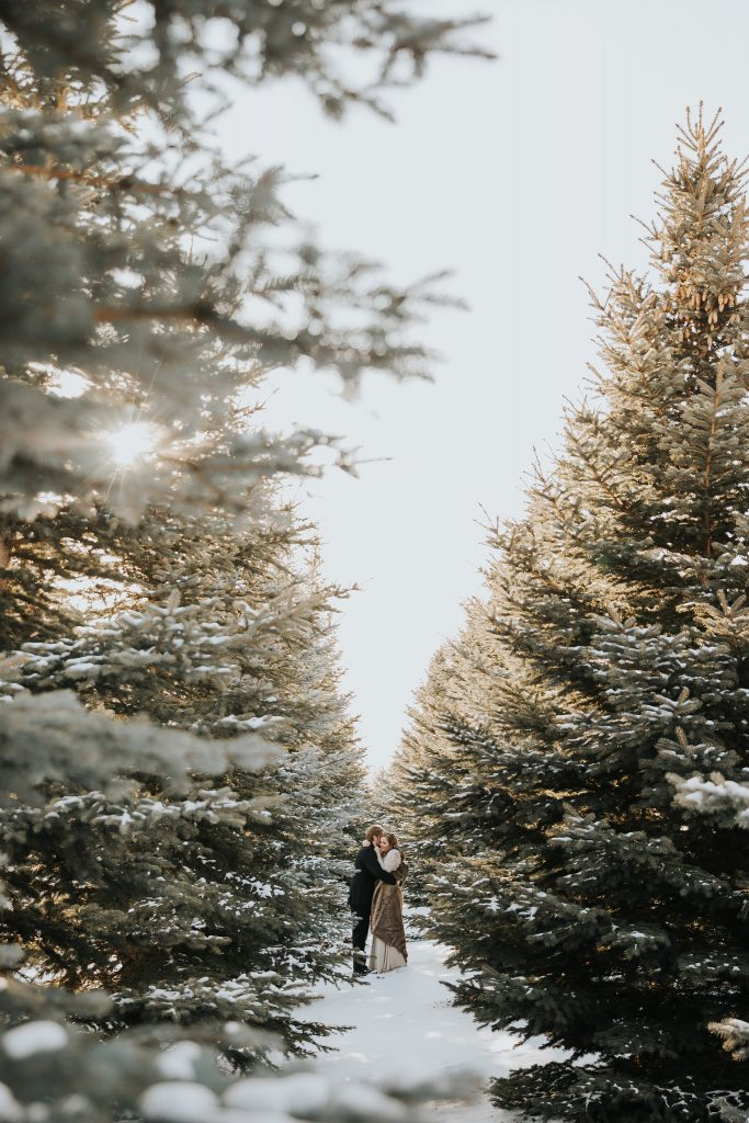 married couple embracing in snow surrounded by trees medicine hat