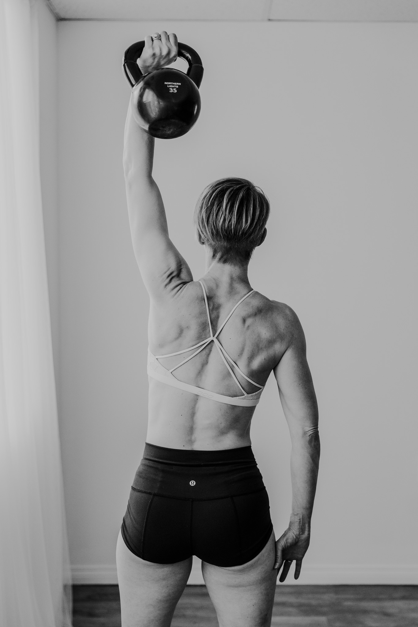 fit woman kettlebell lift one arm hold