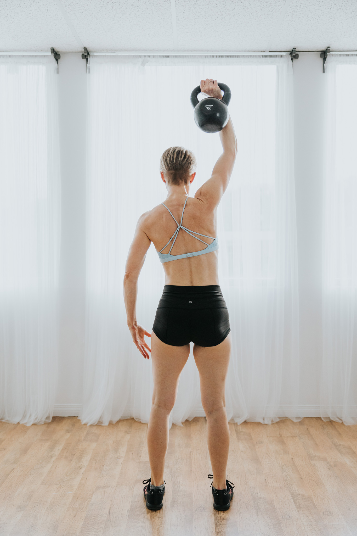 fit woman kettlebell swing single arm raise