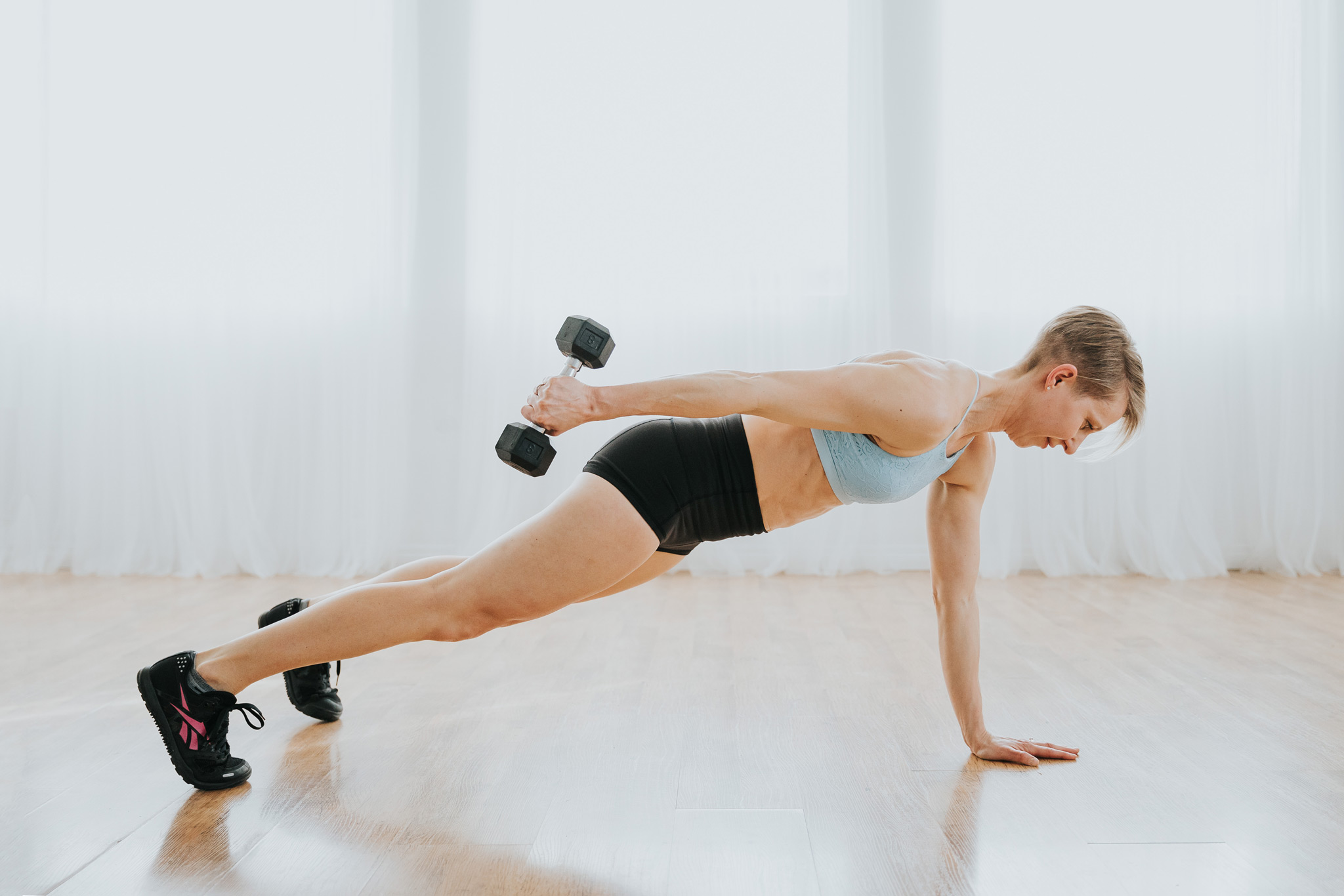 woman working out plank dumbbell row