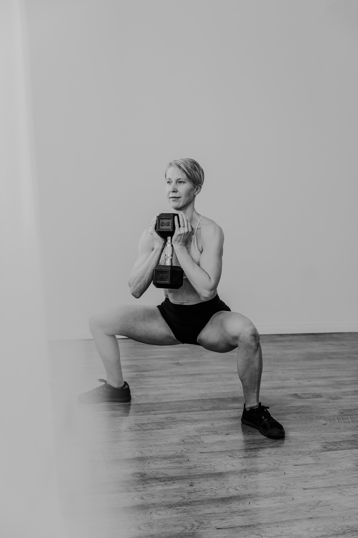 woman in sumo squat with dumbbell
