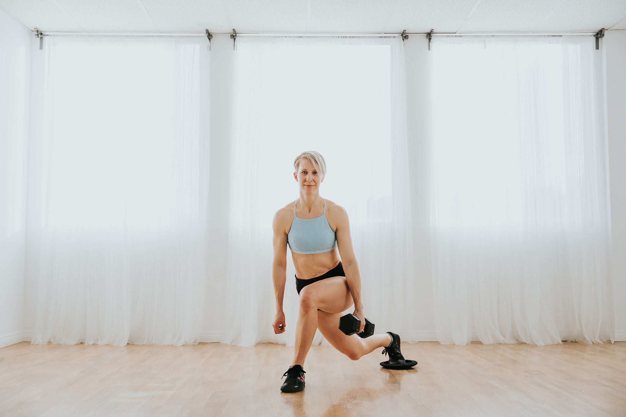 woman in cross leg squat with dumbbell