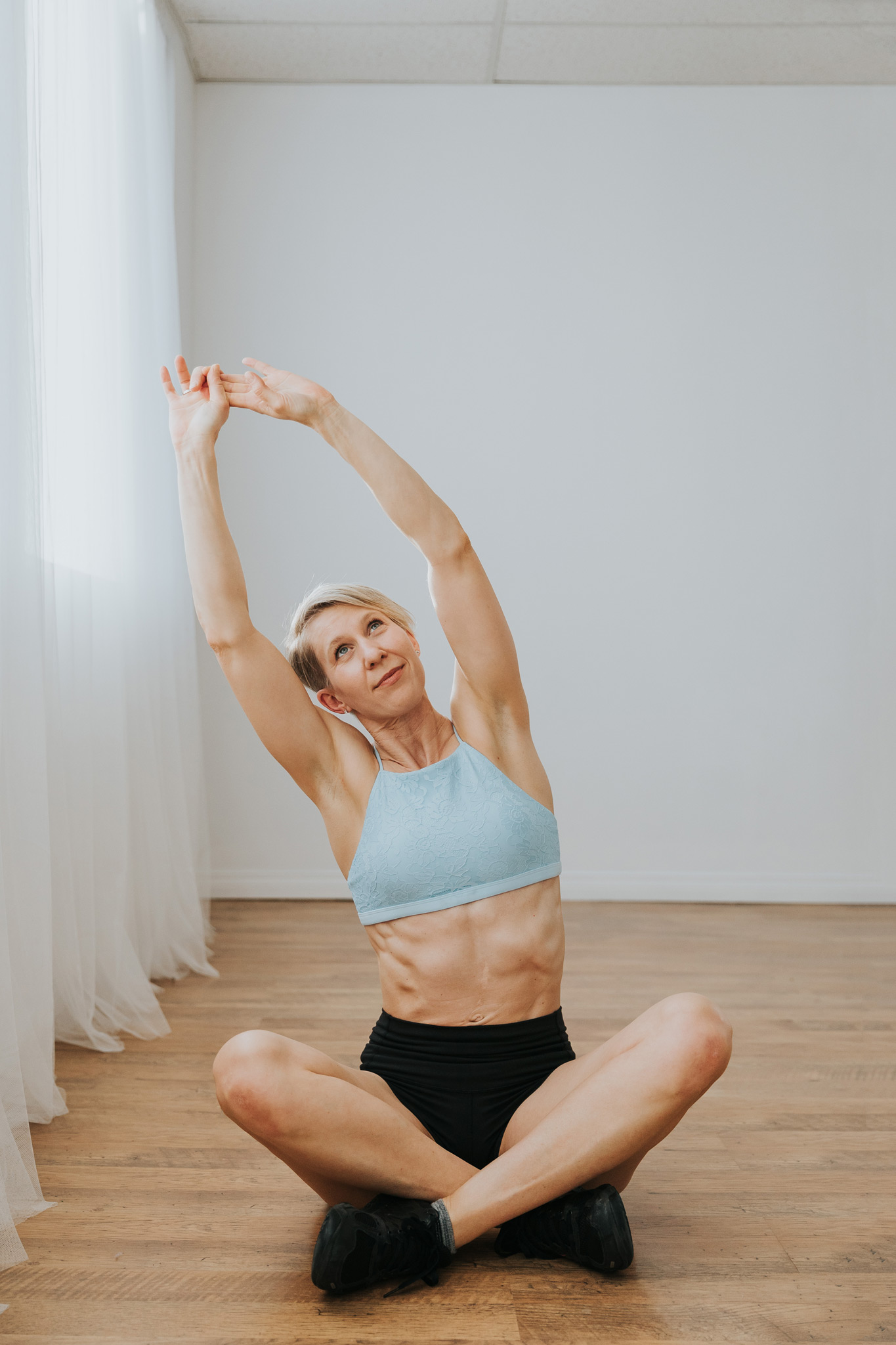woman sitting cross legged and stretching arms leaning