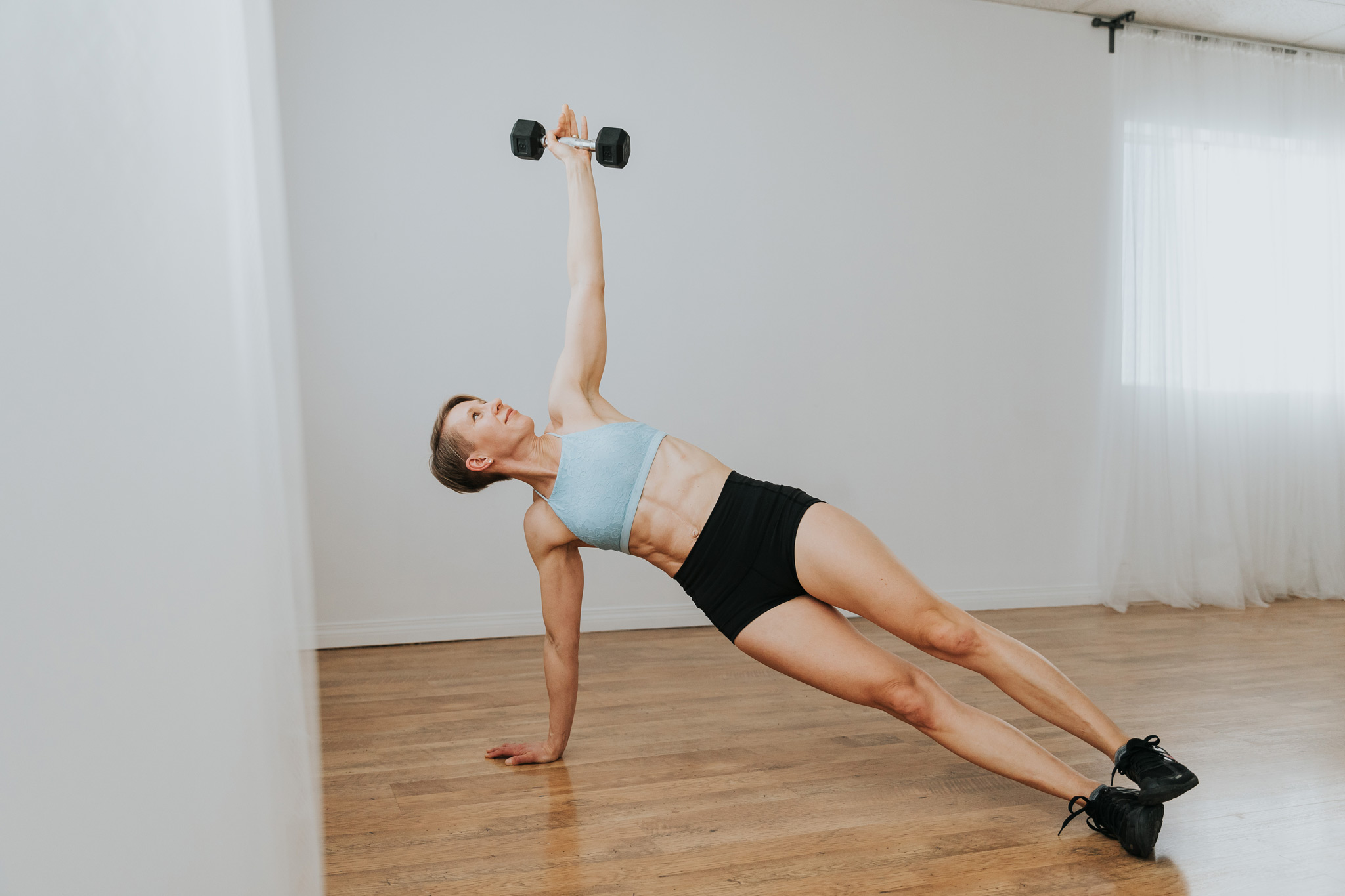 woman in side plank with dumbbell