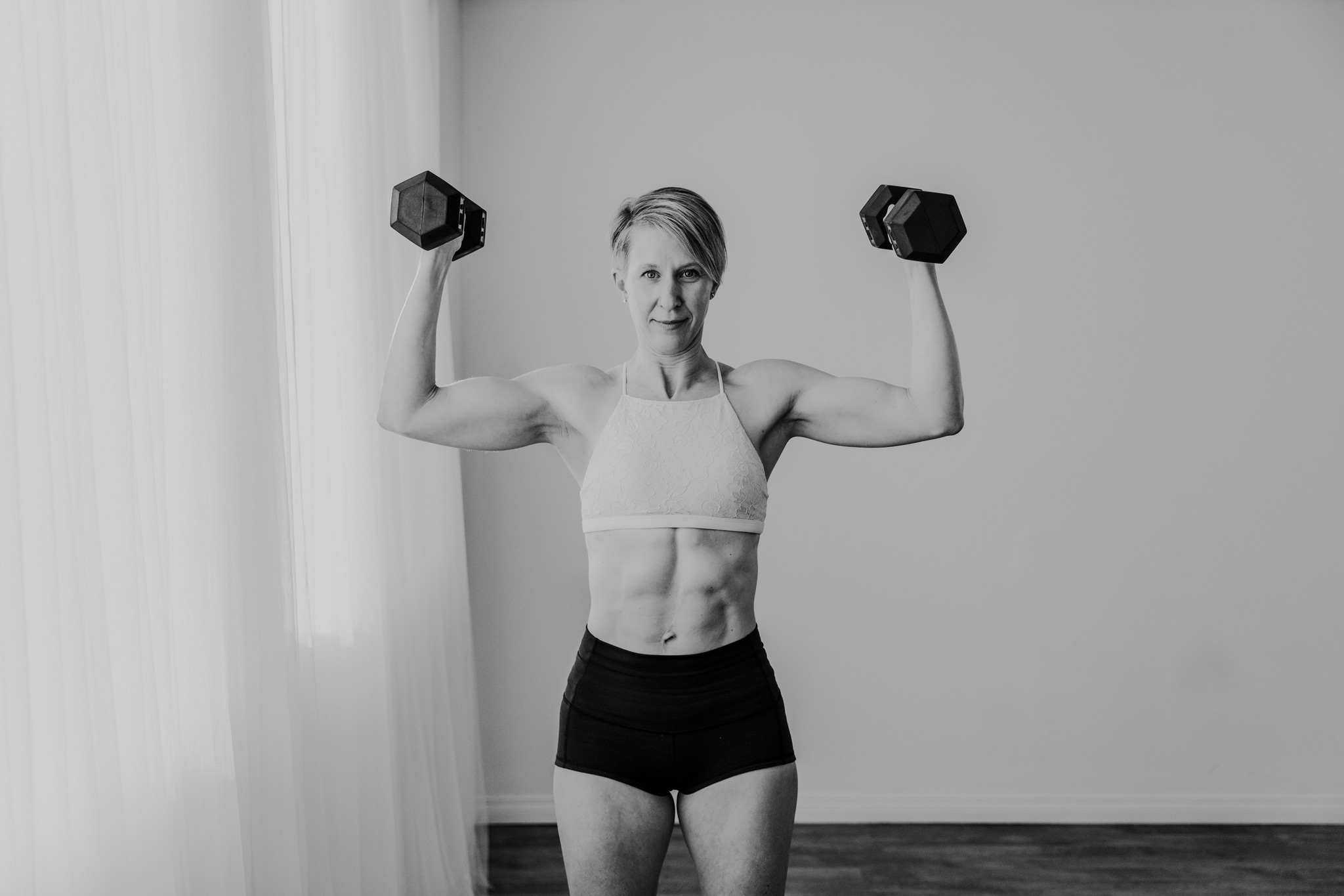 woman holding dumbells up for shoulder press