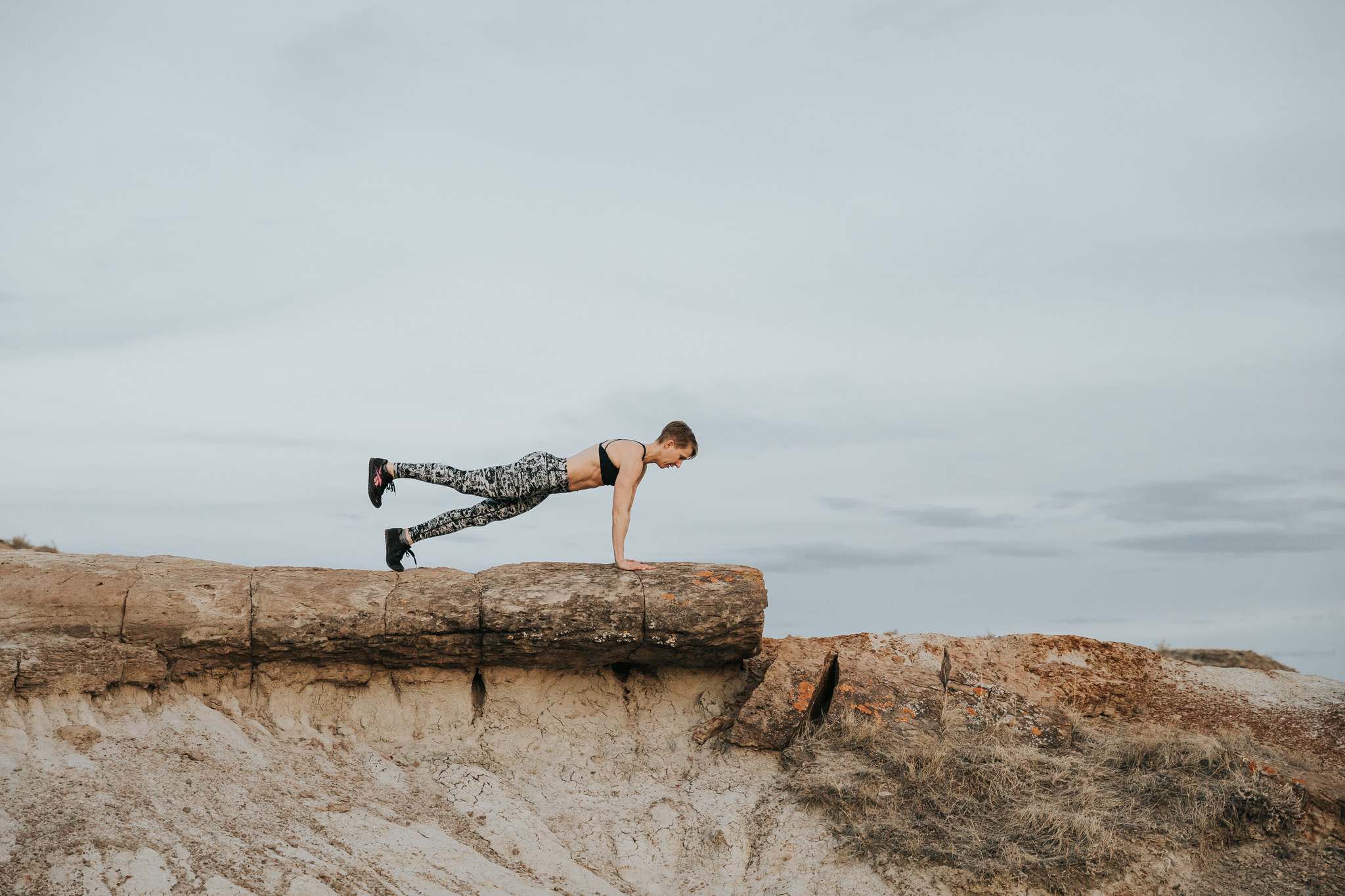 woman on rocky edge in one leg plank