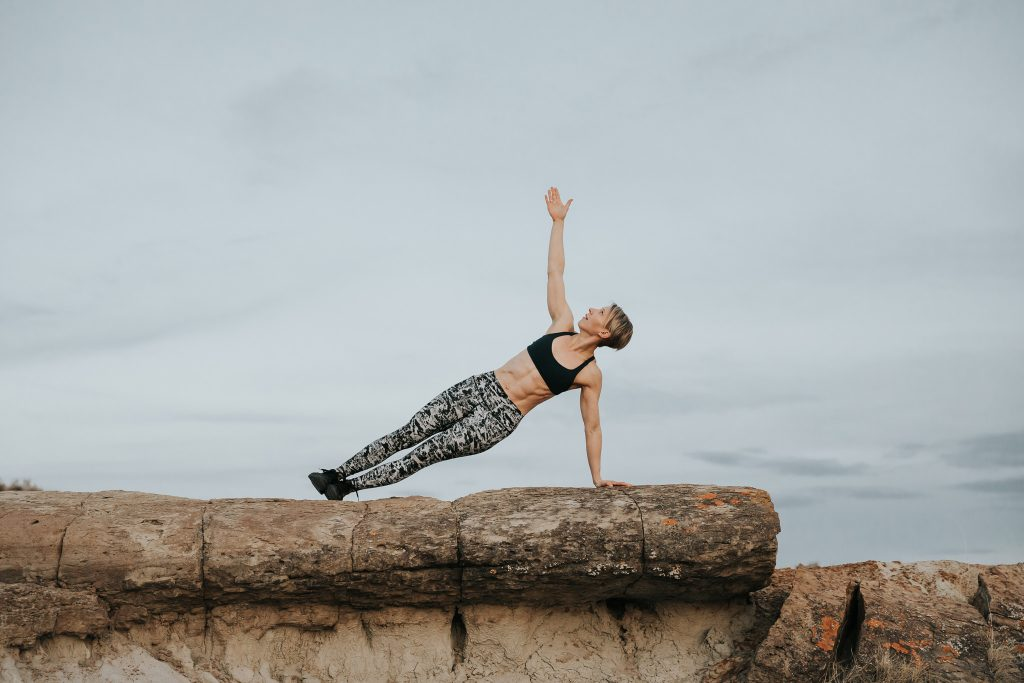 woman on rocky ledge one arm plank