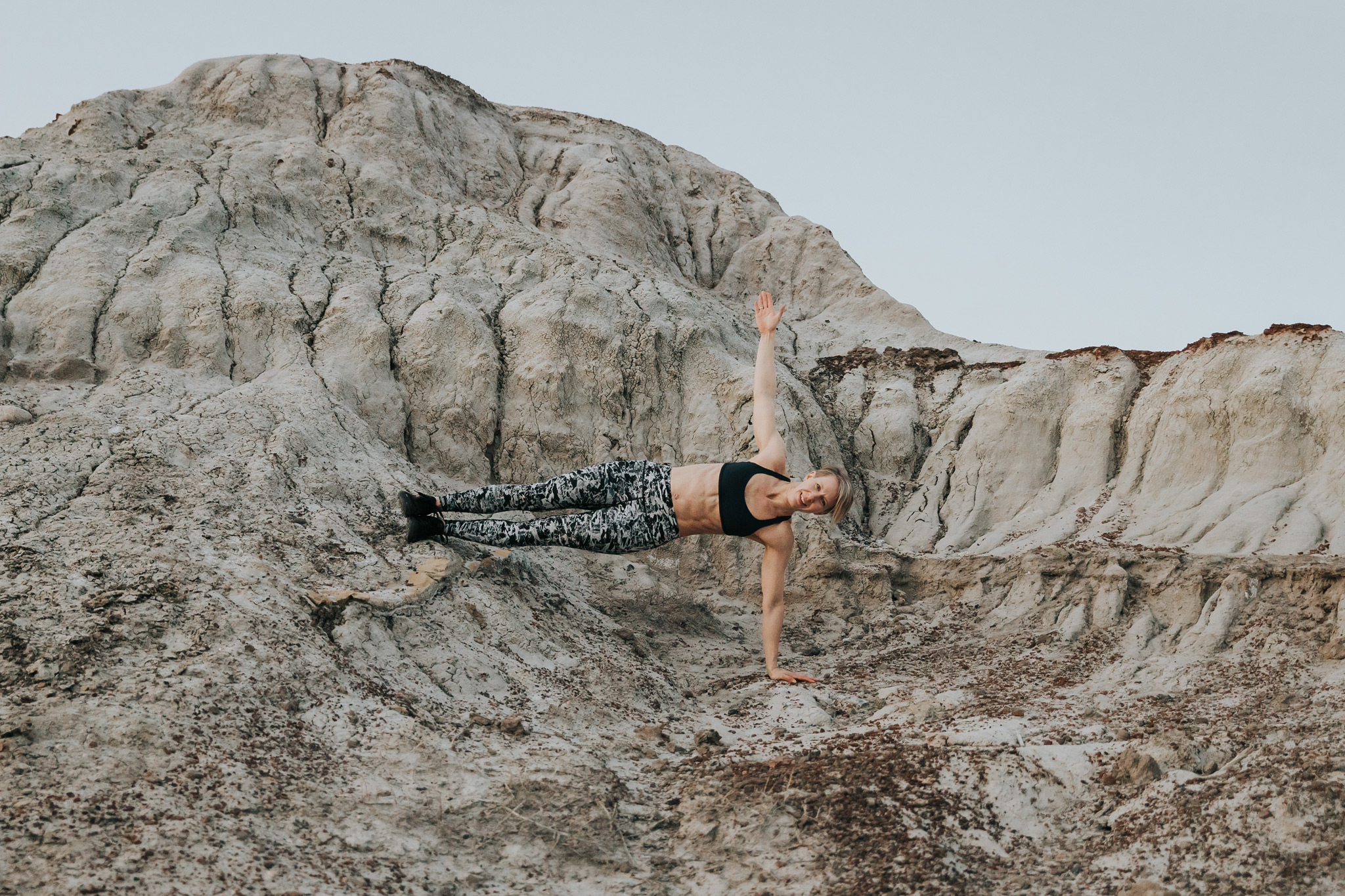 woman holding one arm plank with feet on rocky ledge