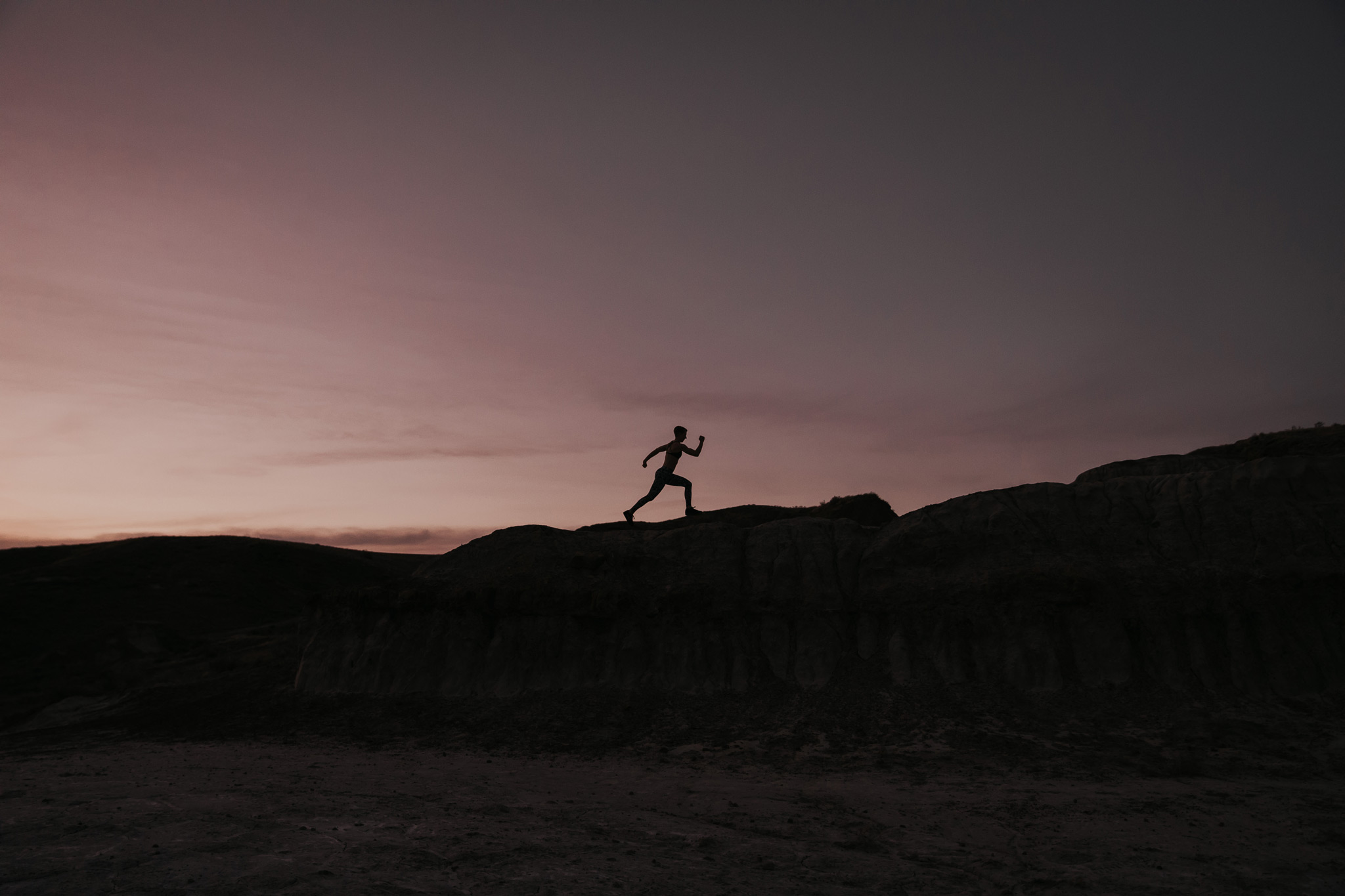 silhouette of woman running across ledge at sunset