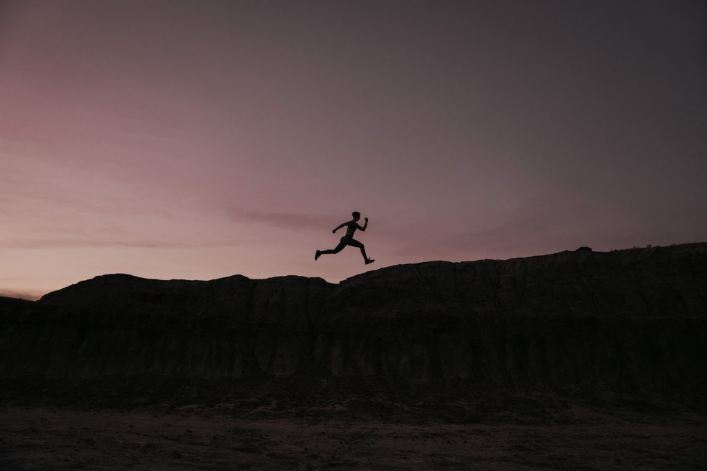 silhouette of woman jumping across ledge at sunset
