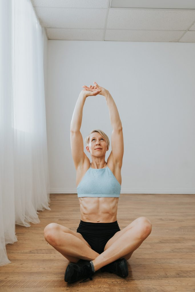woman sitting cross legged and stretching arms up yoga