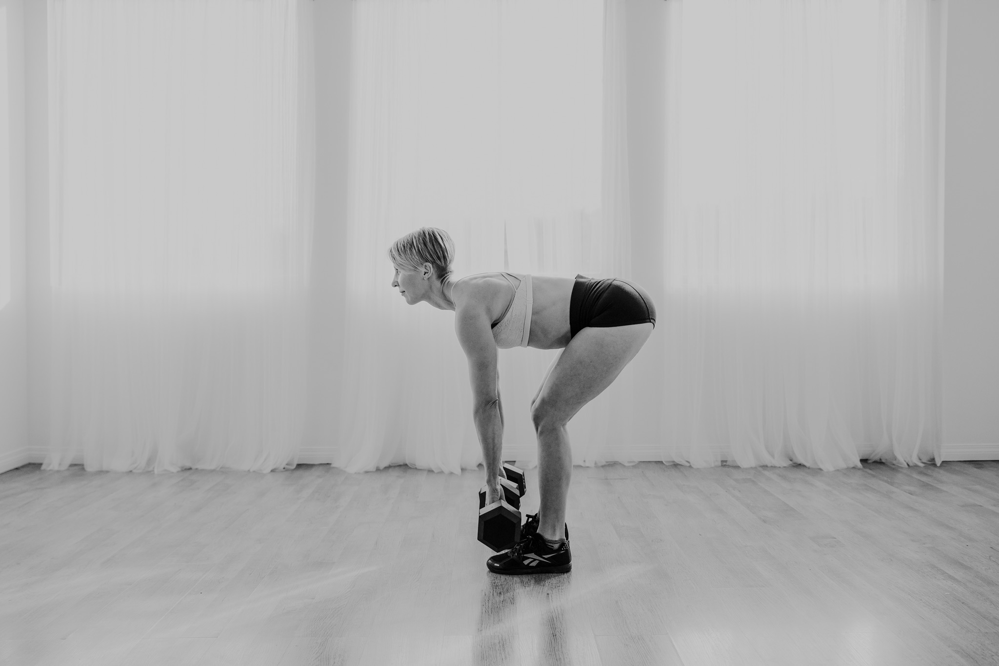 woman working out dumbbell romanian deadlift