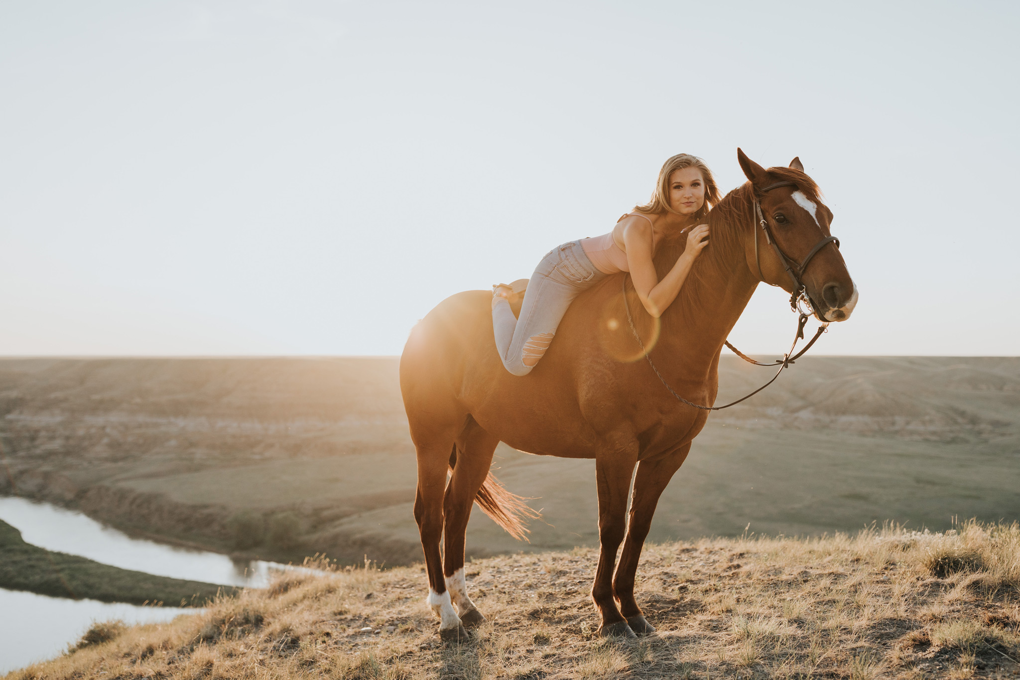 equestrian sunset session girl laying on horse lens flare