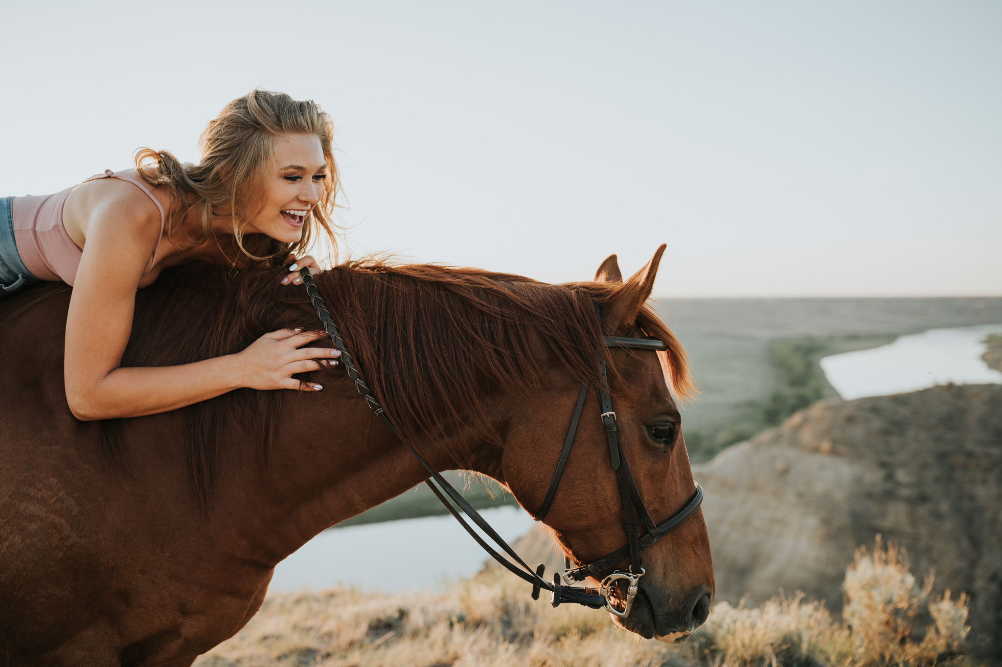 equine session girl laying on horse laughing