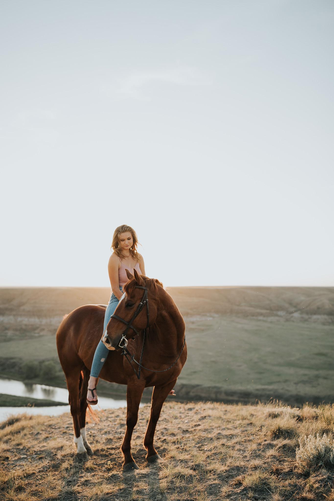 equine senior photo girl sitting on horse alberta coulee sunset