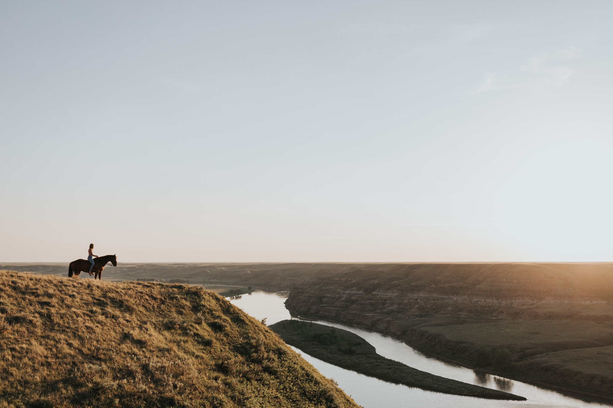 girl on horse overlooking river at sunset