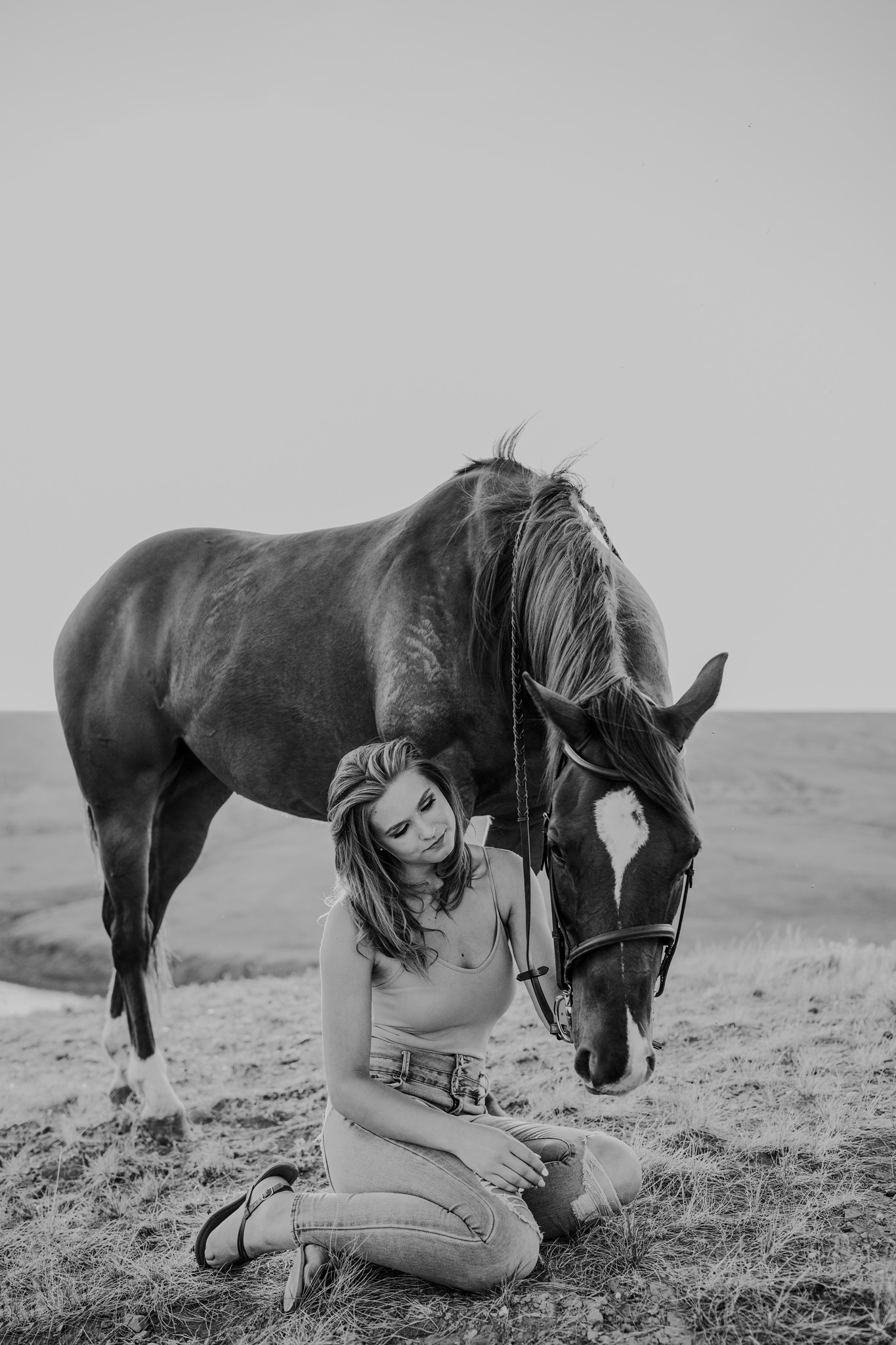 girl sits beside horse equine photo black and white