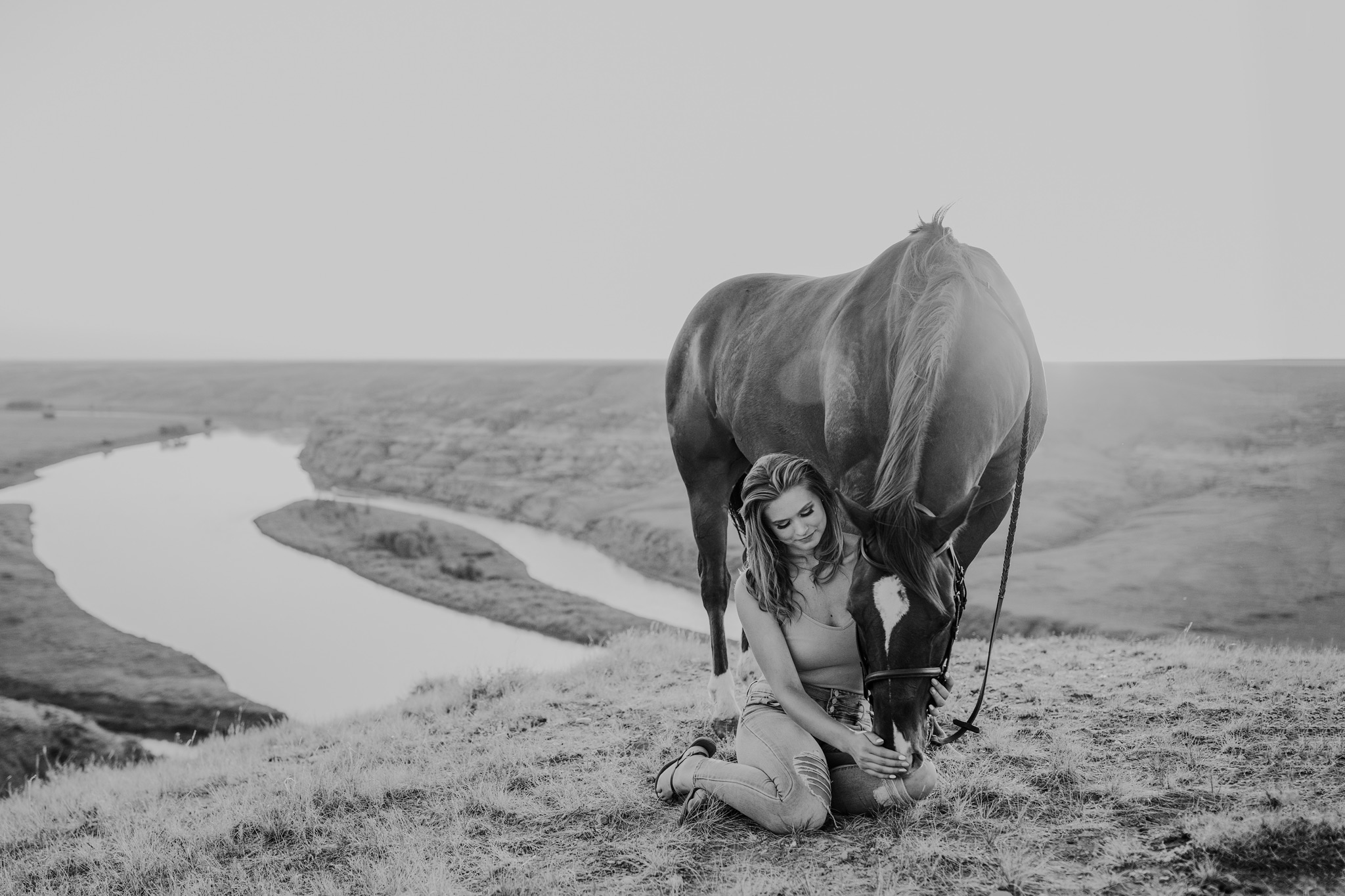 girl sits beside horse at sunset view of coulee river black and white